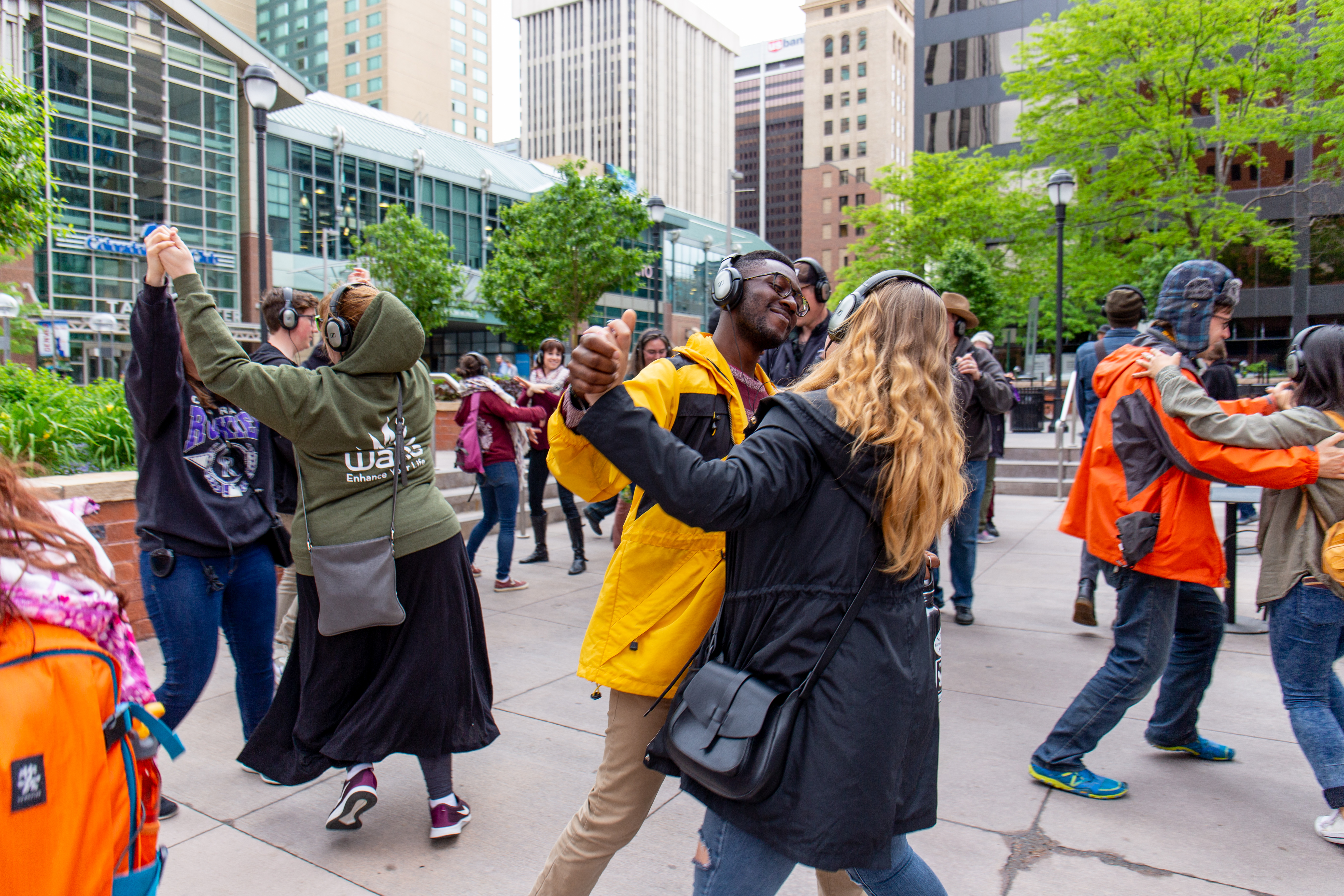 A diverse group of people wear headphones and dance with each other in an urban area.