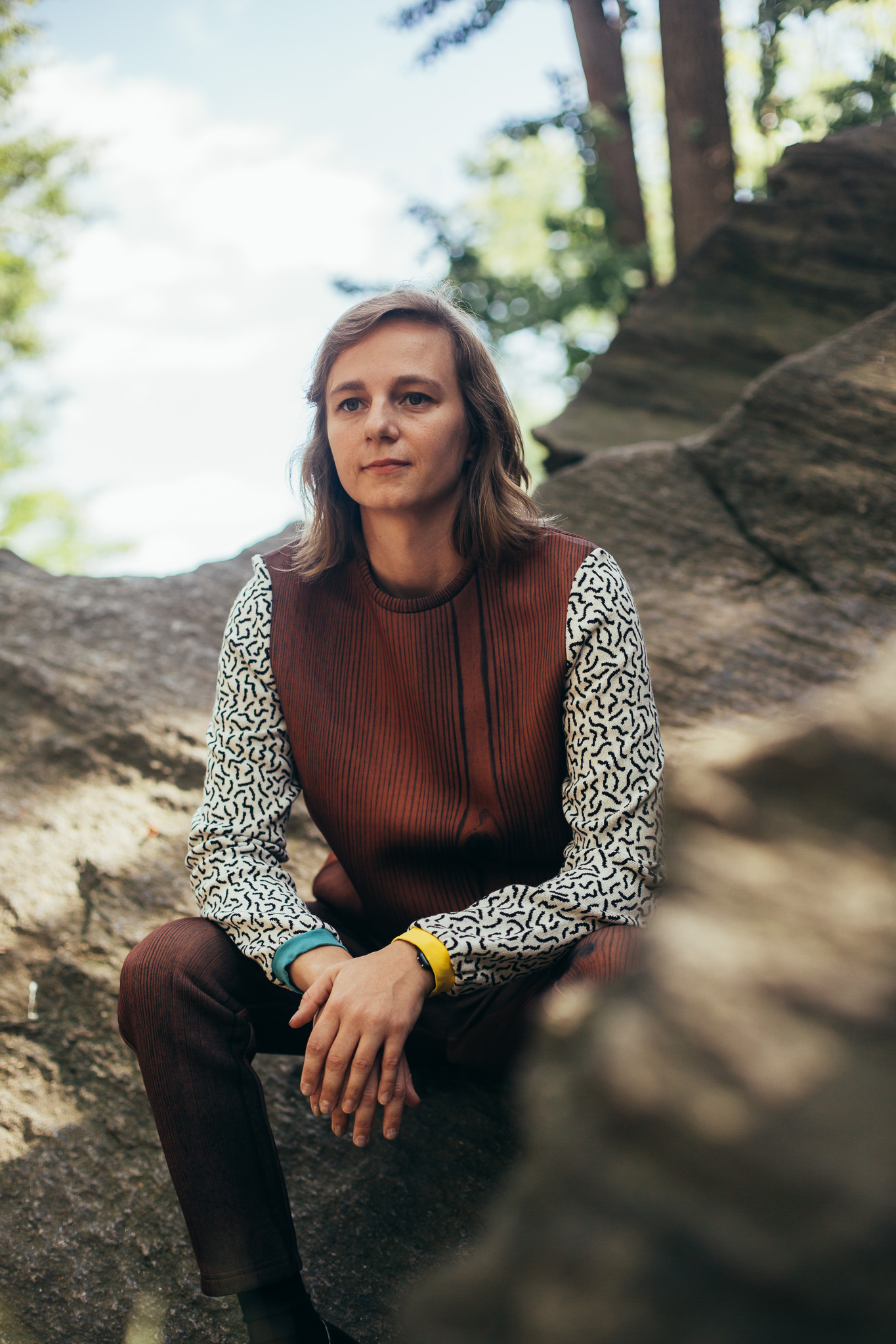 Portrait of Shannon sitting outside on a sunny day among large, flat rocks, smiling softly and looking off in another direction. She is wearing a wood grain sweatshirt and pant set. The sweatshirt has contrasting sleeves with a squiggle pattern and sleeve cuffs in two different colors.