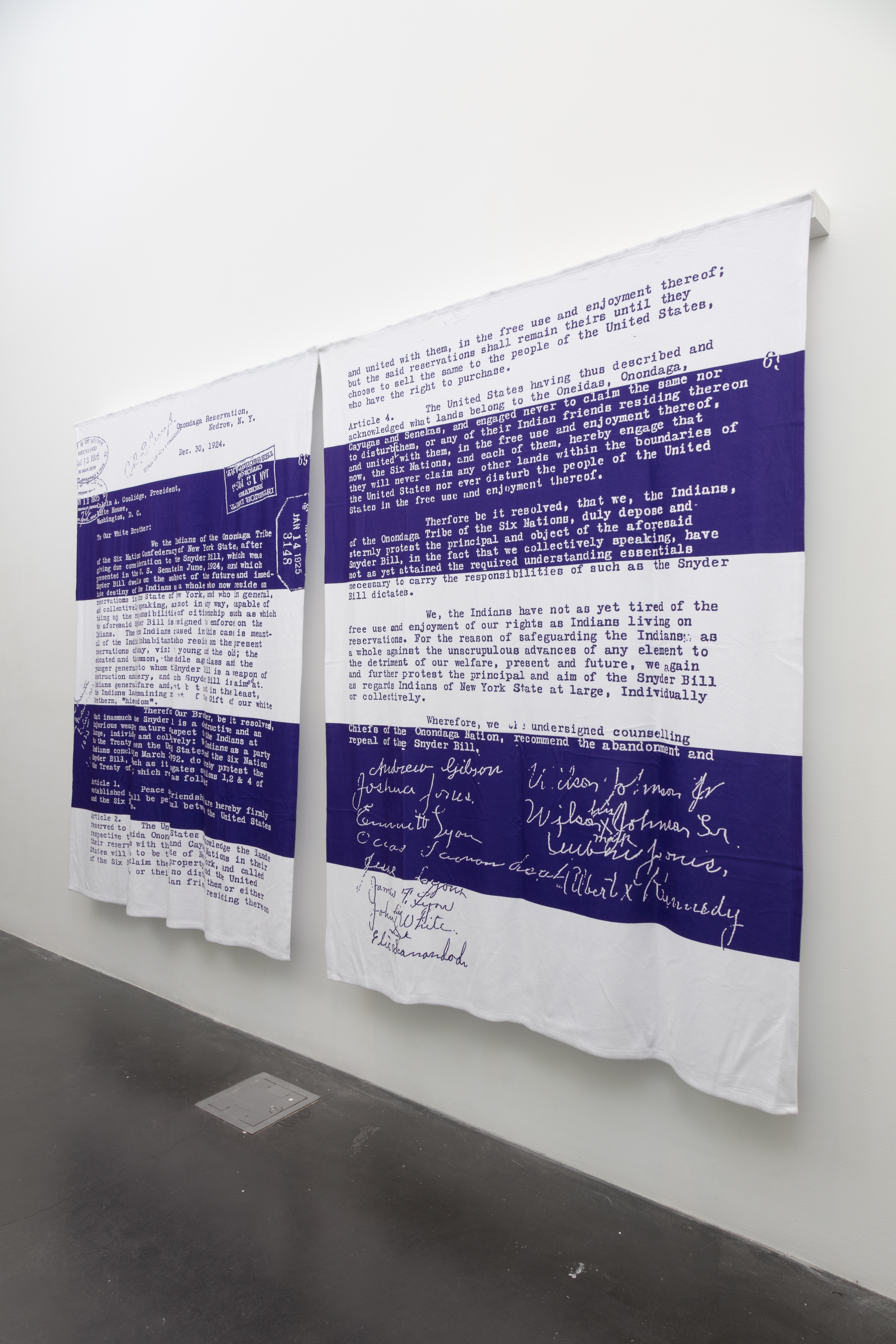 [Image description Artist Alan Michelson's, artwork of a reproduction of the December 30, 1924 letter to Calvin Coolidge by the chiefs of the Onondaga Nation, protesting the Indian Citizenship Act and reaffirming Onondaga sovereignty. The reproduction is on a pair of blankets in the colors white and purple and hangs on a white gallery wall with a dark concrete floor.]