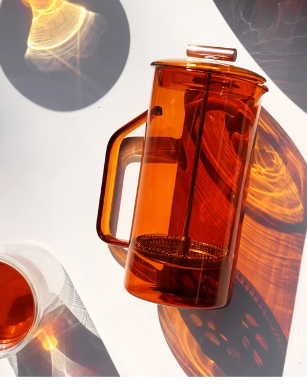 an orange glass french press, laying on a table in direct sunlight.