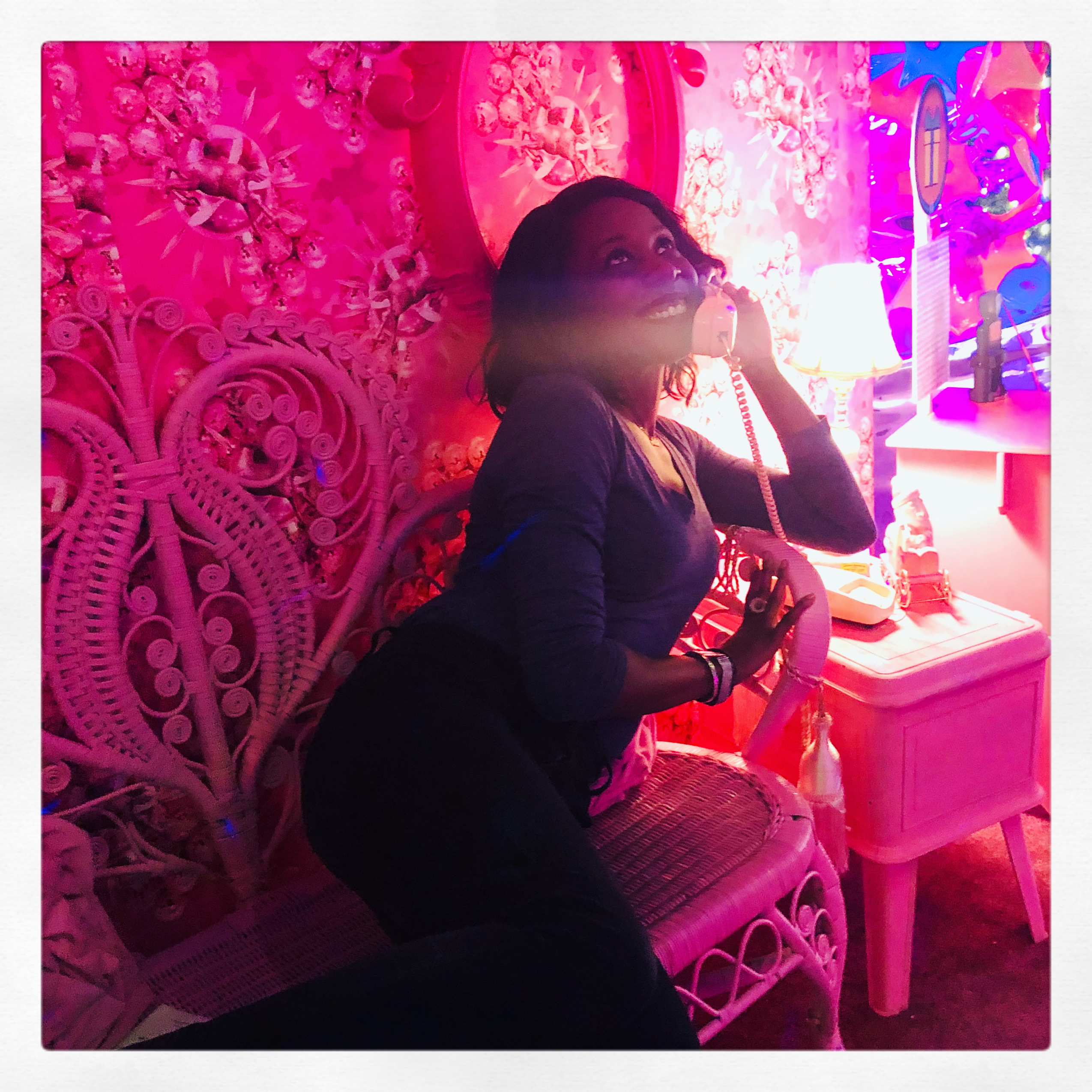 portrait of Tai in an eclectic, pink colored room. She's lounging on a bench and is holding up a corded landline phone, looking up and smiling.