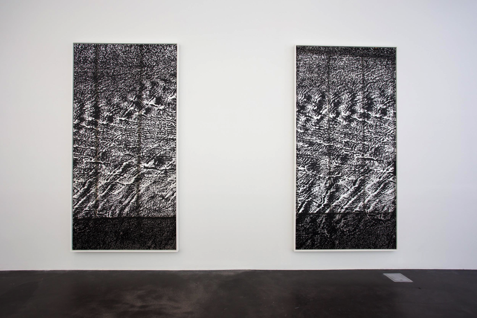 Two abstract grainy artworks in black and white resemble sand dunes are waves of water. They hang vertically against a white wall in a gallery.