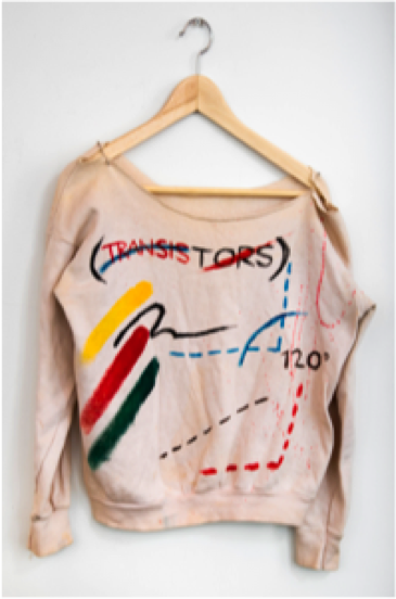 An off white colored sweater hangs on a wood clothes hanger on a white wall. It is hand painted with abstract shapes and the words TRANSISTORS is in red near the collar.