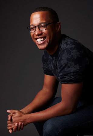Playwright, Branden Jacobs Jenkins, sitting angled in blue jeans and dark tee shirt, hands clasped and his has a joyful smile.