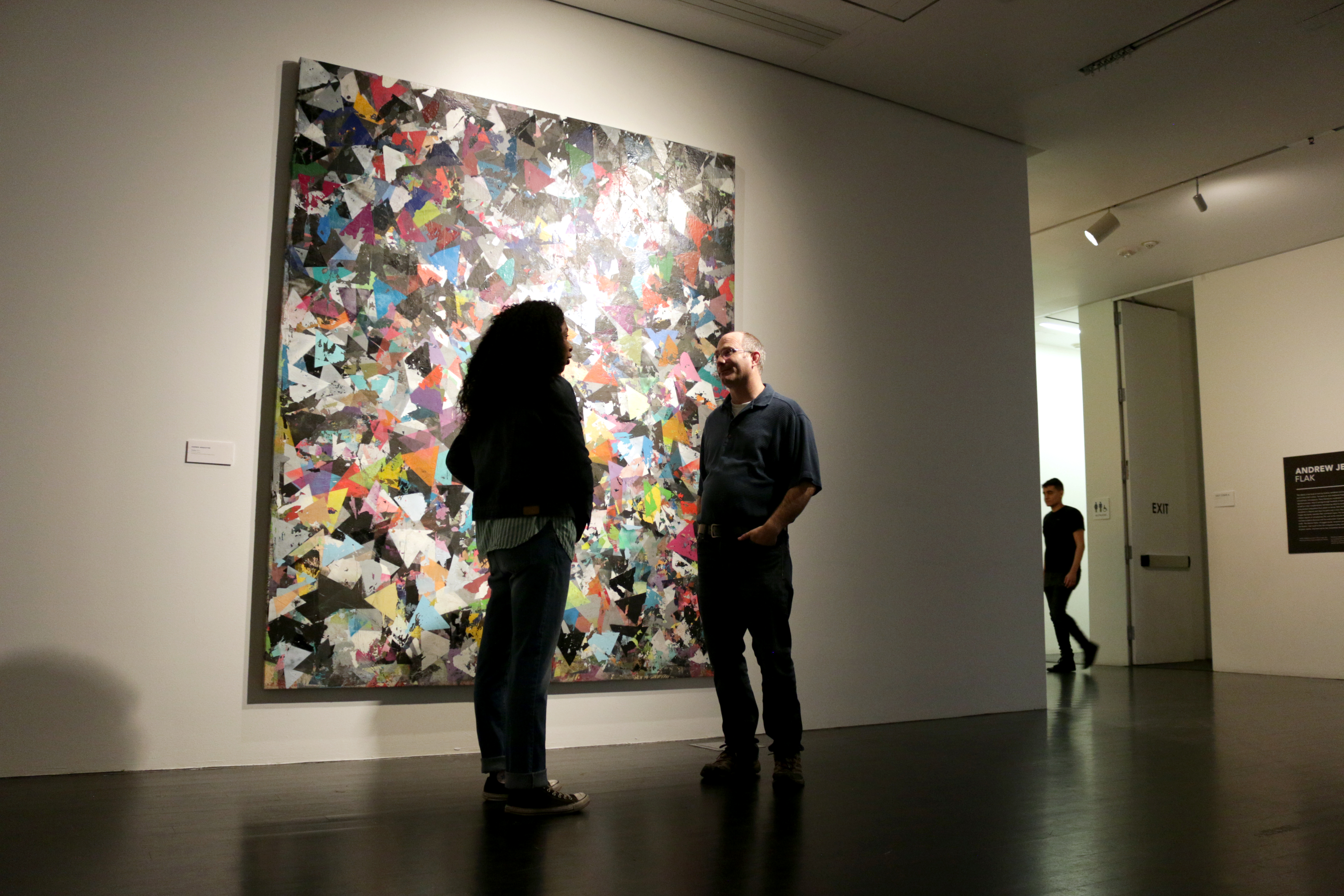 Two people talk in front of an abstract artwork in a dimly lit gallery.