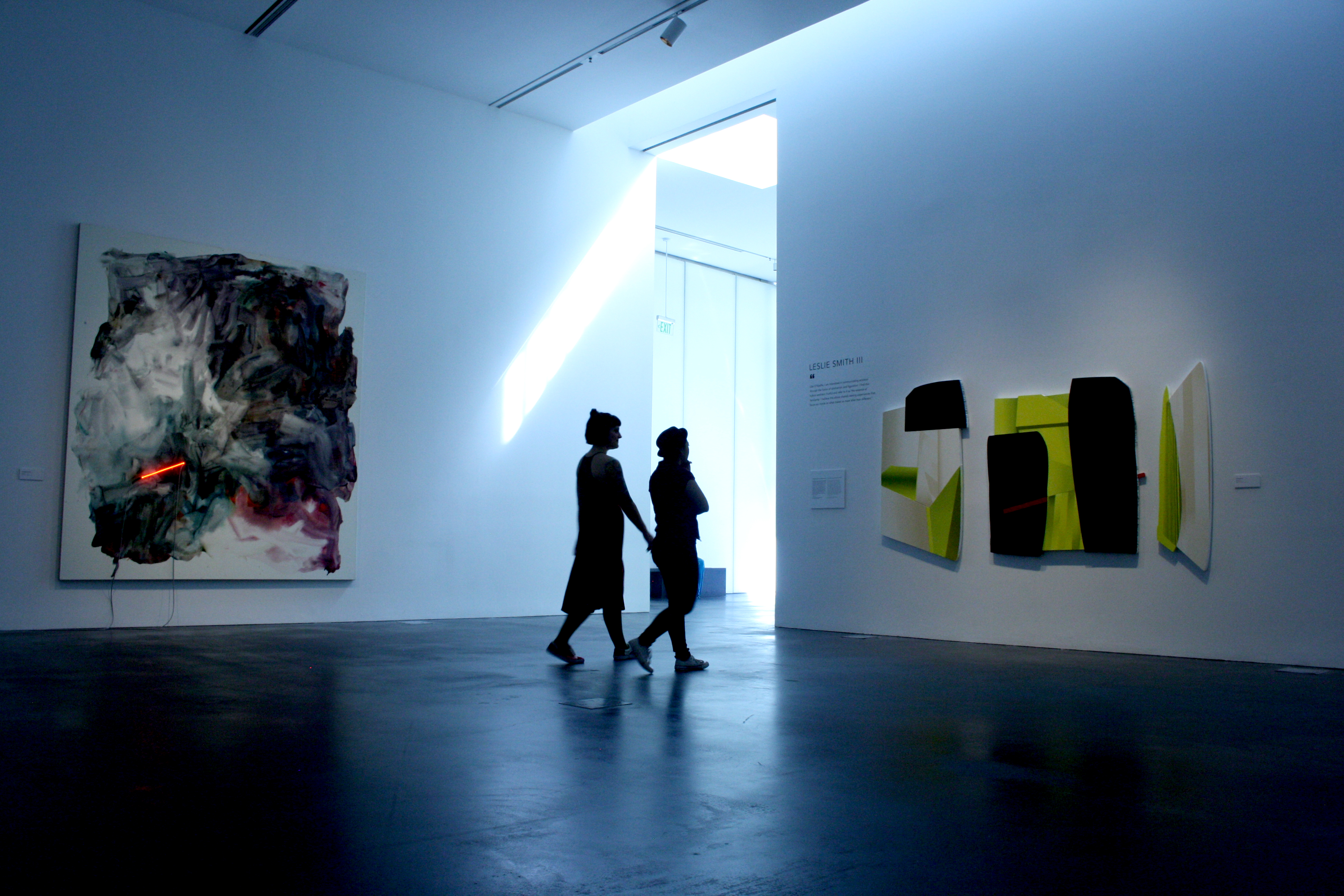 Two unidentifiable people in a gallery look at an abstract artwork. The ceiling is high and the floor is concrete.