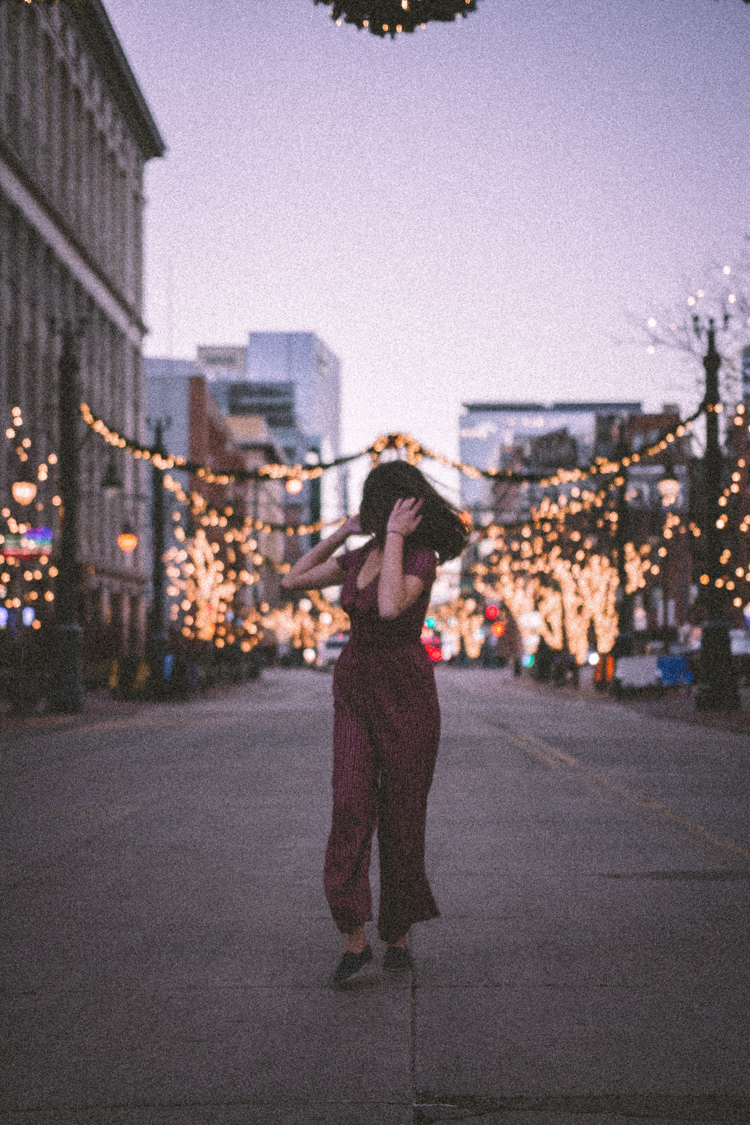 A young woman walks down the middle of a street at dusk. She looks behind her shoulder at holiday lights that adorn the street lamps and trees.