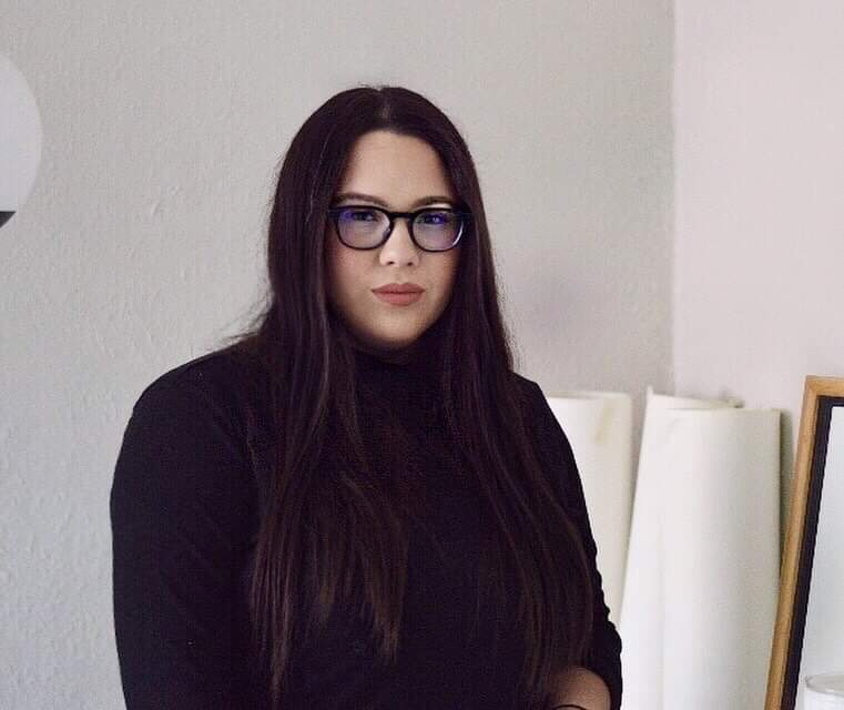 portrait of Alexandra is a room painted in a soft gray color. She is wearing a black turtle neck and glasses with black frames. Her long, straight dark brown hair is parted in the middle, and she has a serious look on her face.
