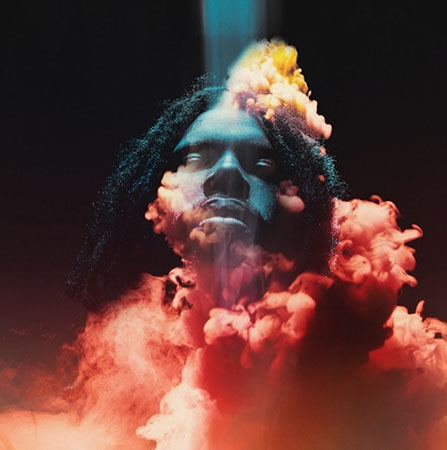 Image of artist, Flying Lotus, with a blue light casting down on hist face, that is engulfed in thick red smoke against a black background