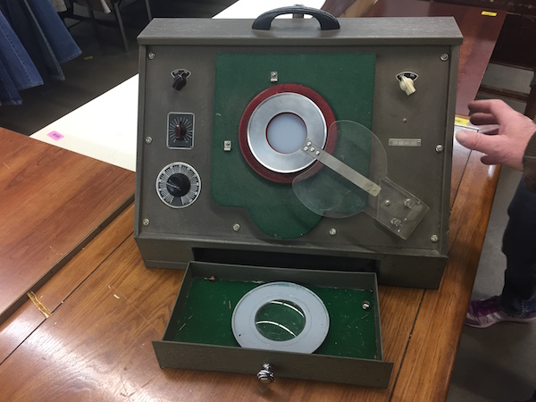 An old electronic instrument of unknown use or purpose. It has three dials on the side and a lens in the center. It is dark green with a handle on the top.