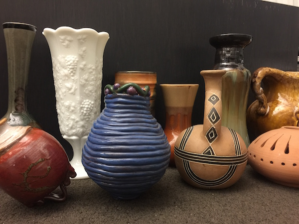 Several works of pottery against a dark backdrop. They vary in color and design but are all small sized vessels.
