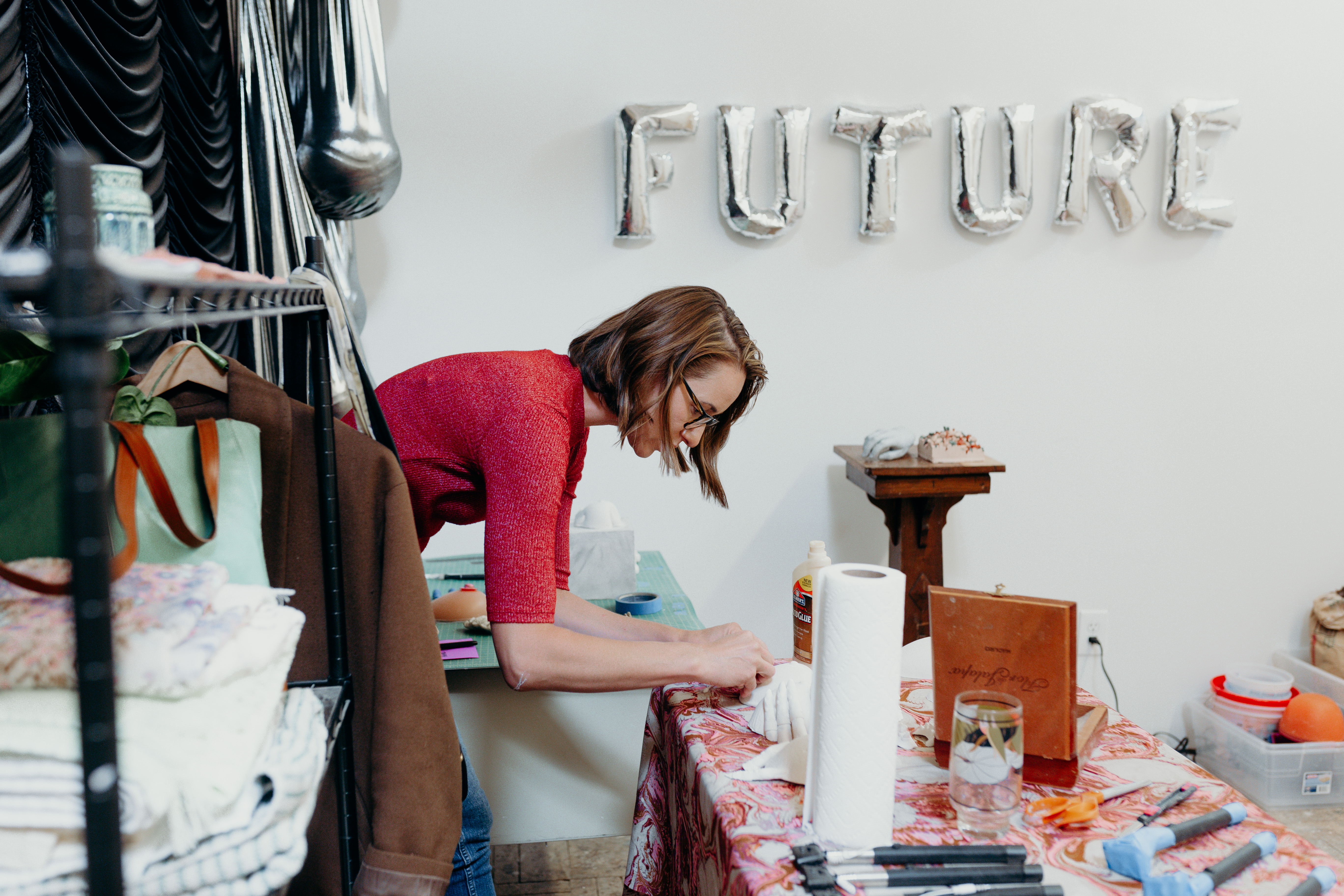 Candid shot of Laura shill working at a table. The words Future are spelled out behind her in silver balloons.