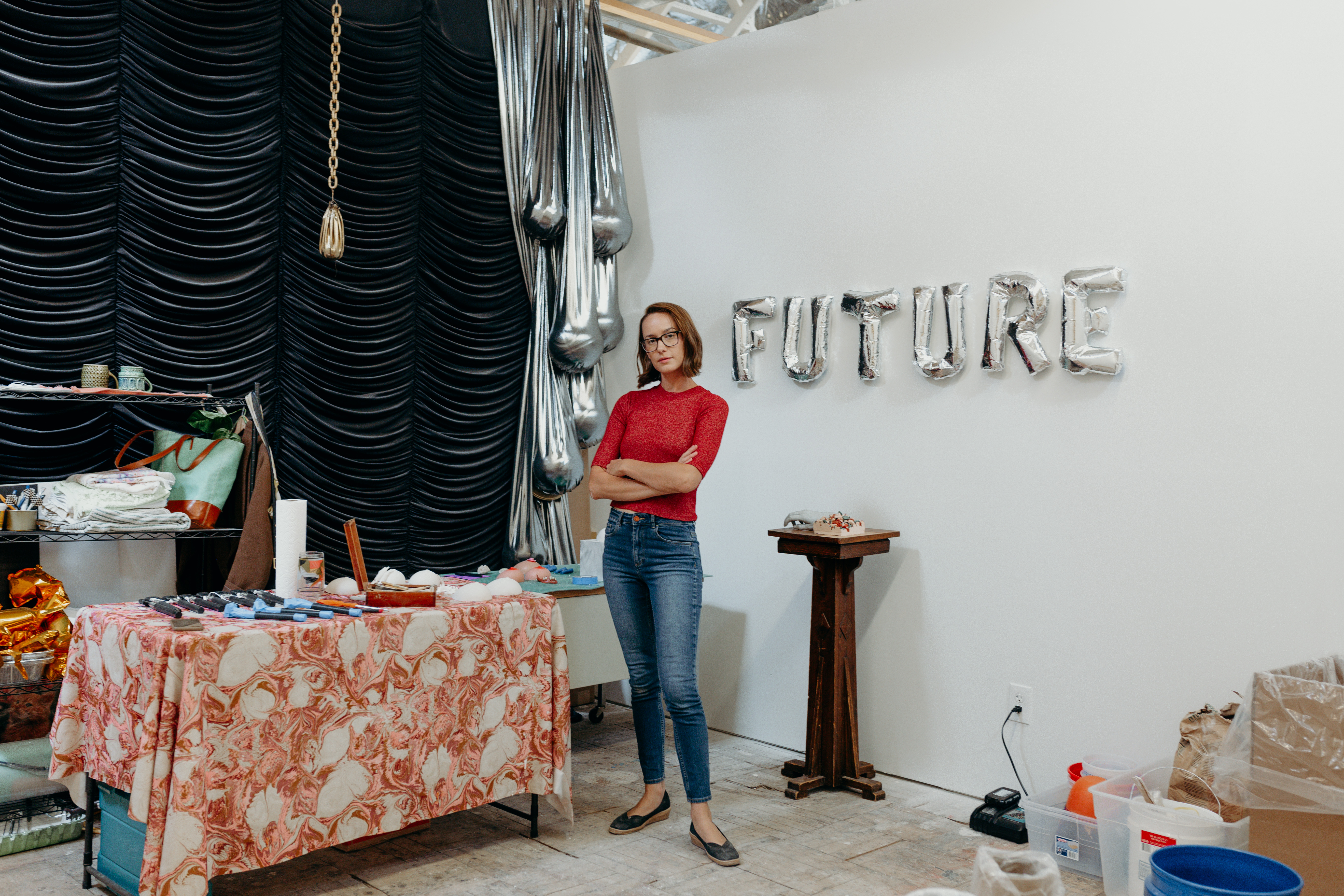 Laura Shills poses in her studio with her arms crossed in front of her. Behind her on a white wall are silver balloons spelling out the word Future.