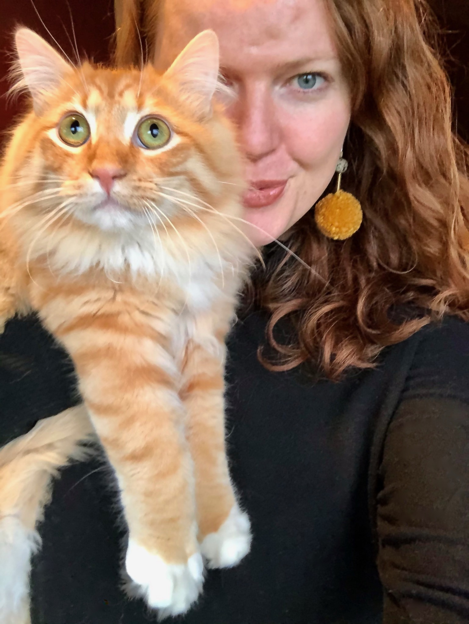 selfie of Krista with her cat. She is piercing her lips and is wearing a black turtle neck, yellow pom-pom earrings, and her red short hair is in curls. Her cat's coloring is orange and white, and the cat has green eyes, which appear aghast.