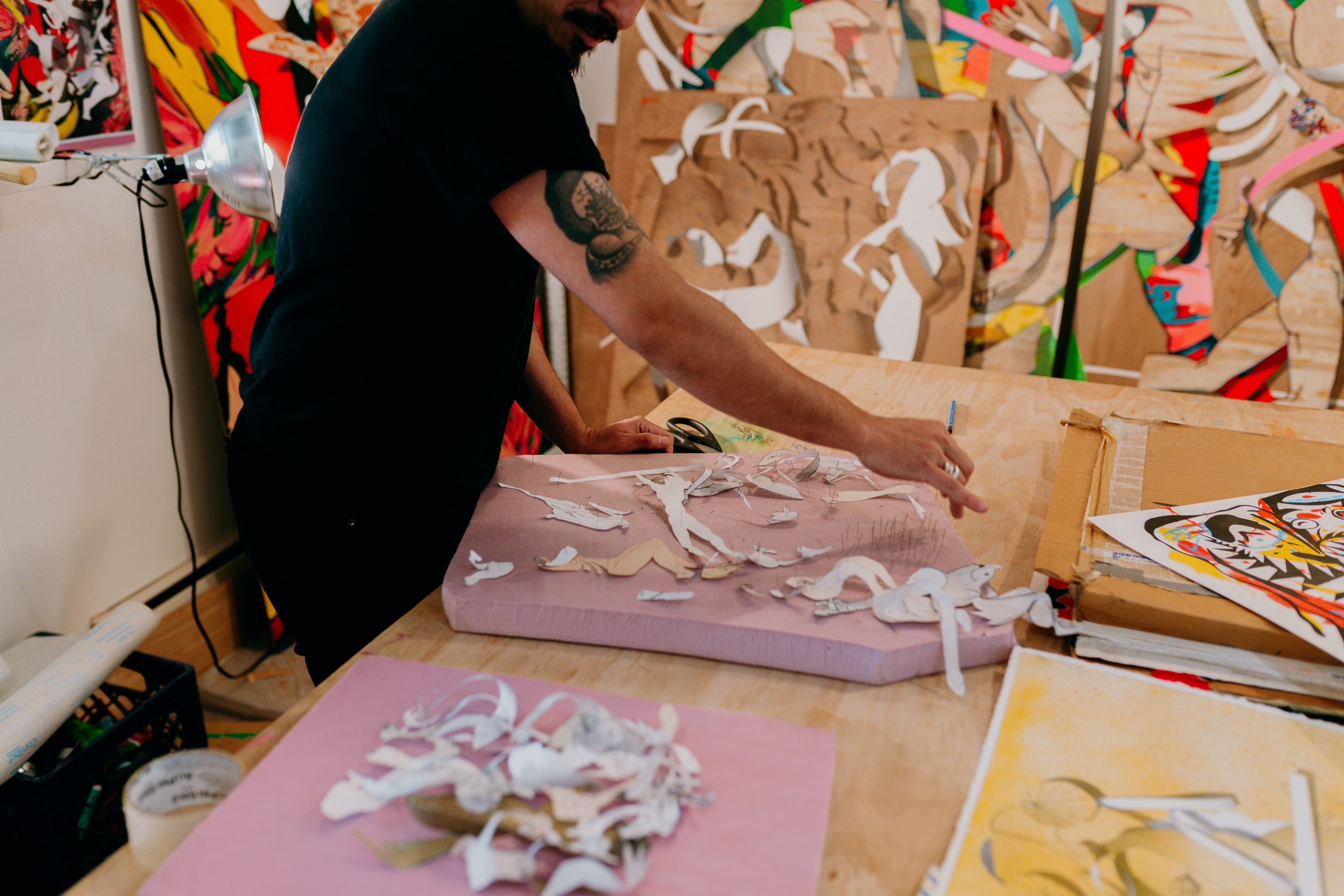 Candid shot of a man working in a studio surrounded by wood panel artworks and styrofoam .