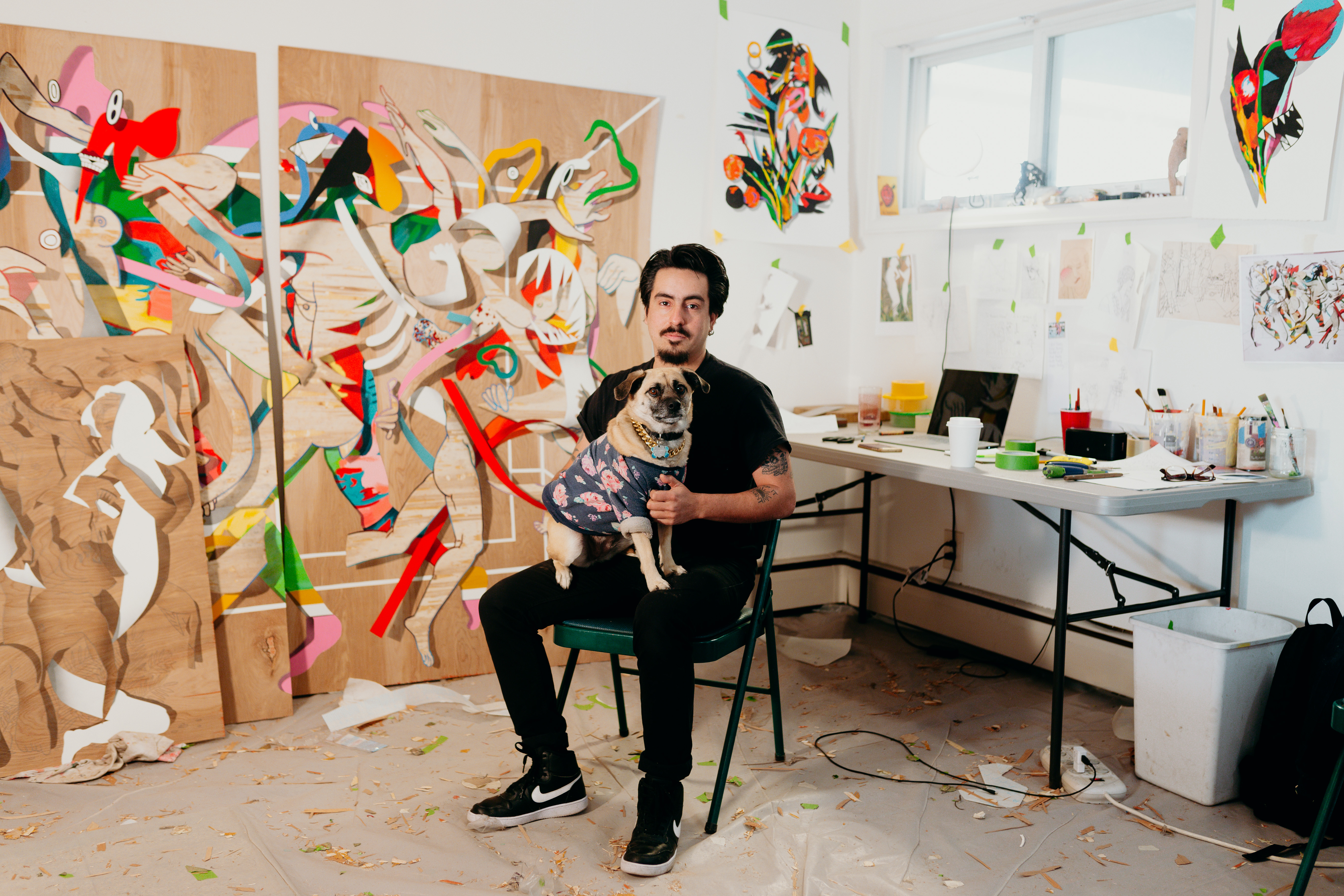 A man sits in a chair with a small dog in his lap in a studio space with  large paintings resting against the walls.