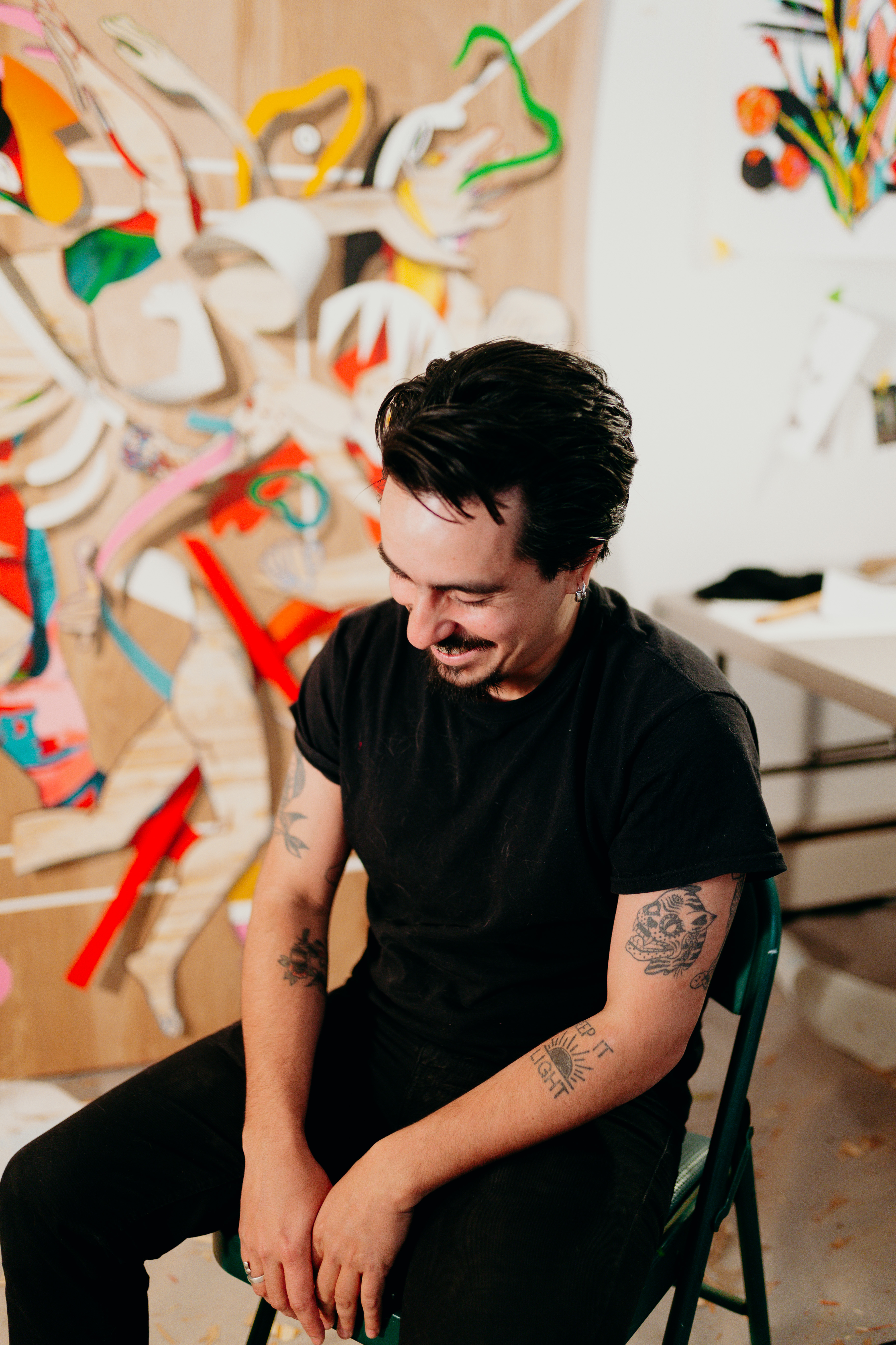 Portrait of a man sitting on a chair in a studio space. He is wearing a black t shirt and black pants. He is mid laugh