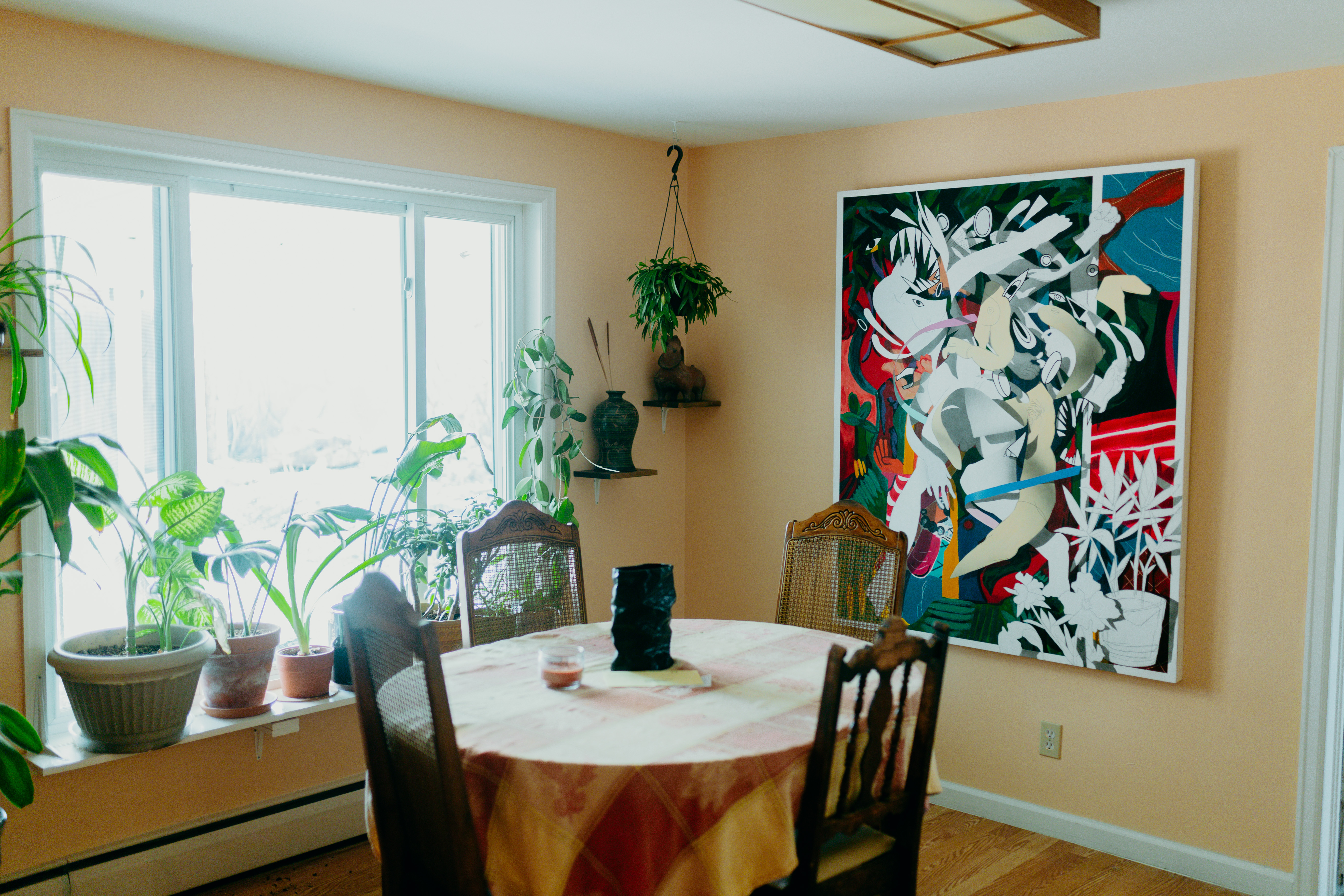 A dining room filled with plants. On the wall is a large abstract painting. A round table with four chairs rests in the center of the room.