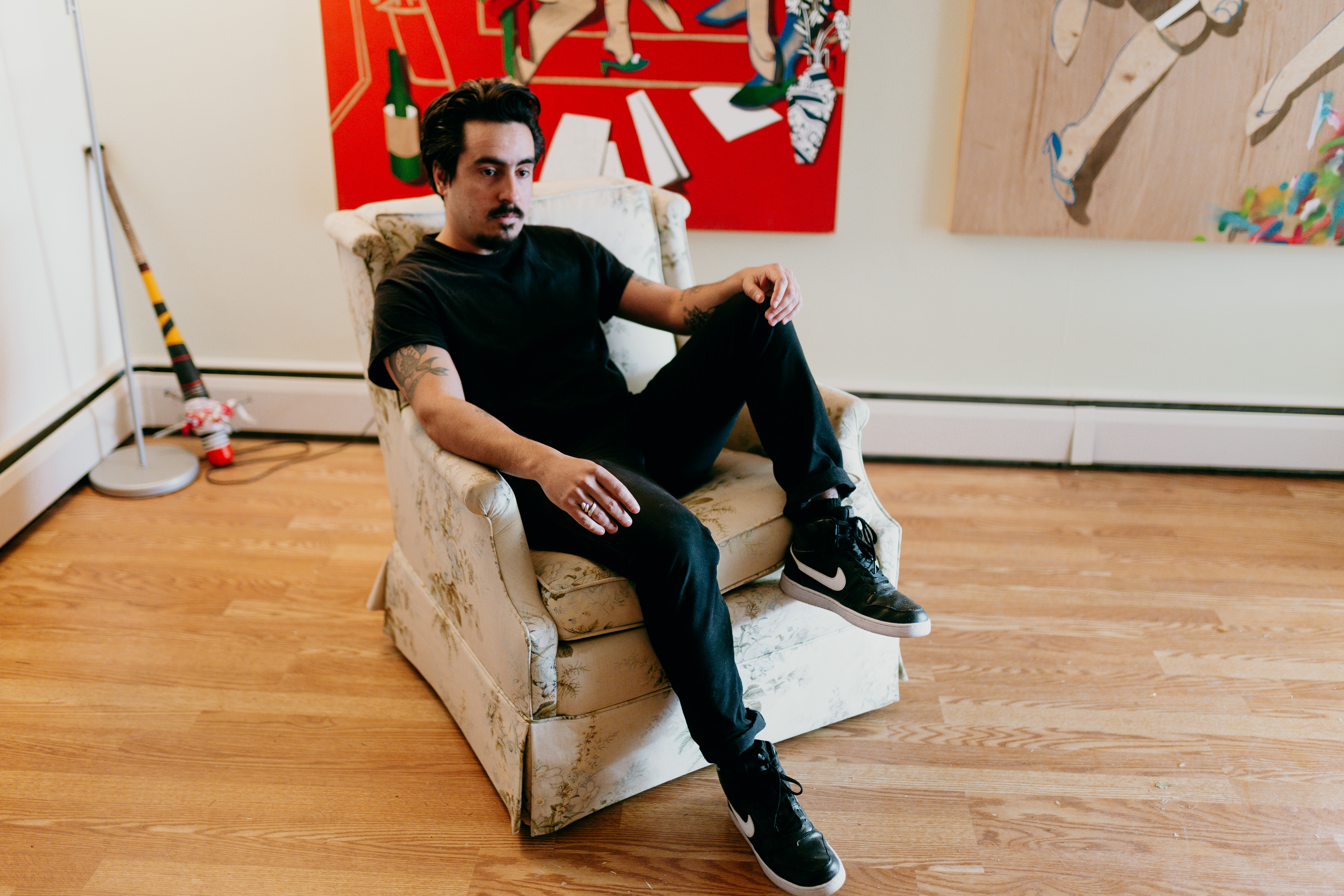 A man in all black sits on a couch in an indoor space.