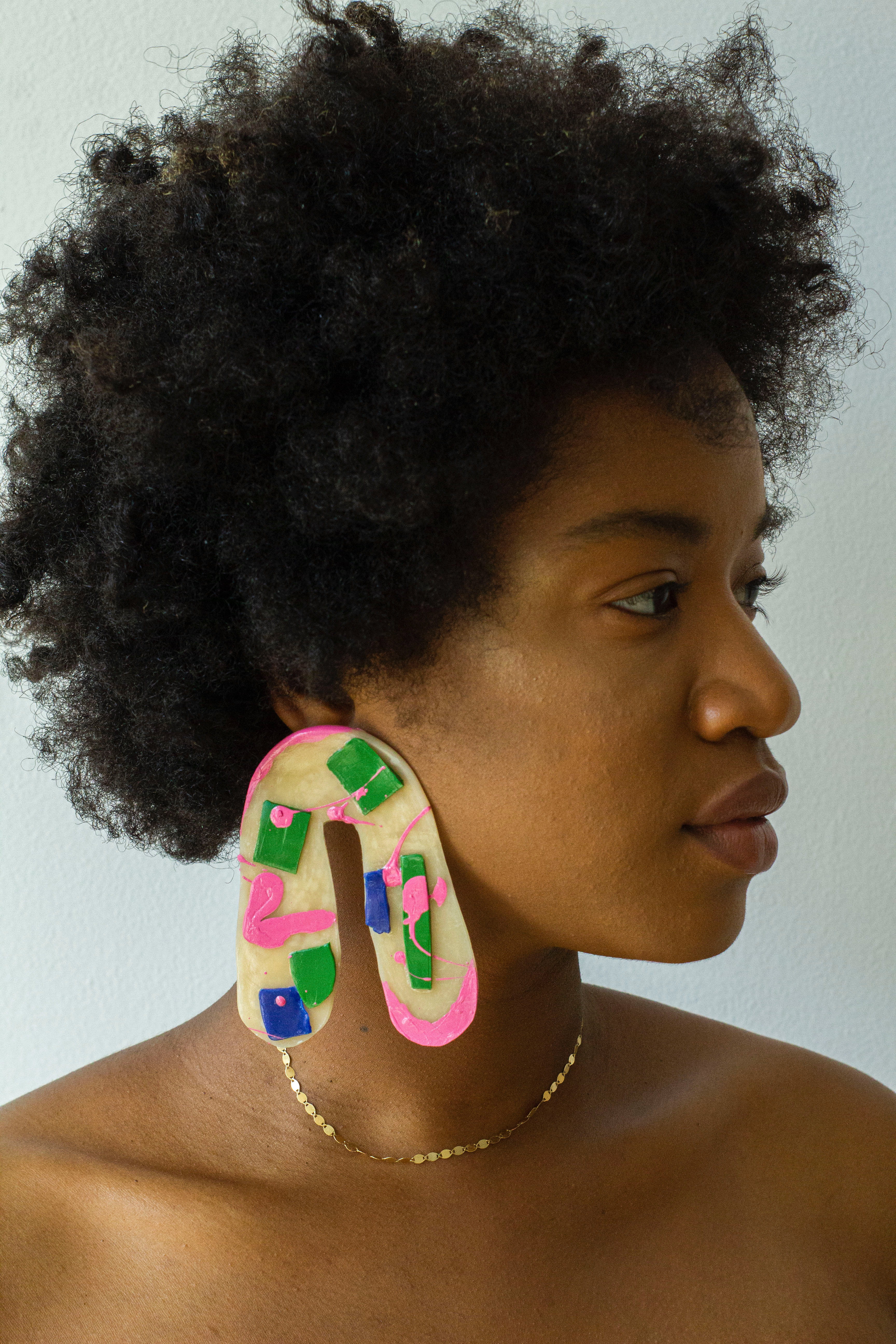 Close up portrait of Jaylan Rose, wearing big arch shaped earrings that are beige, pink, blue, and green.