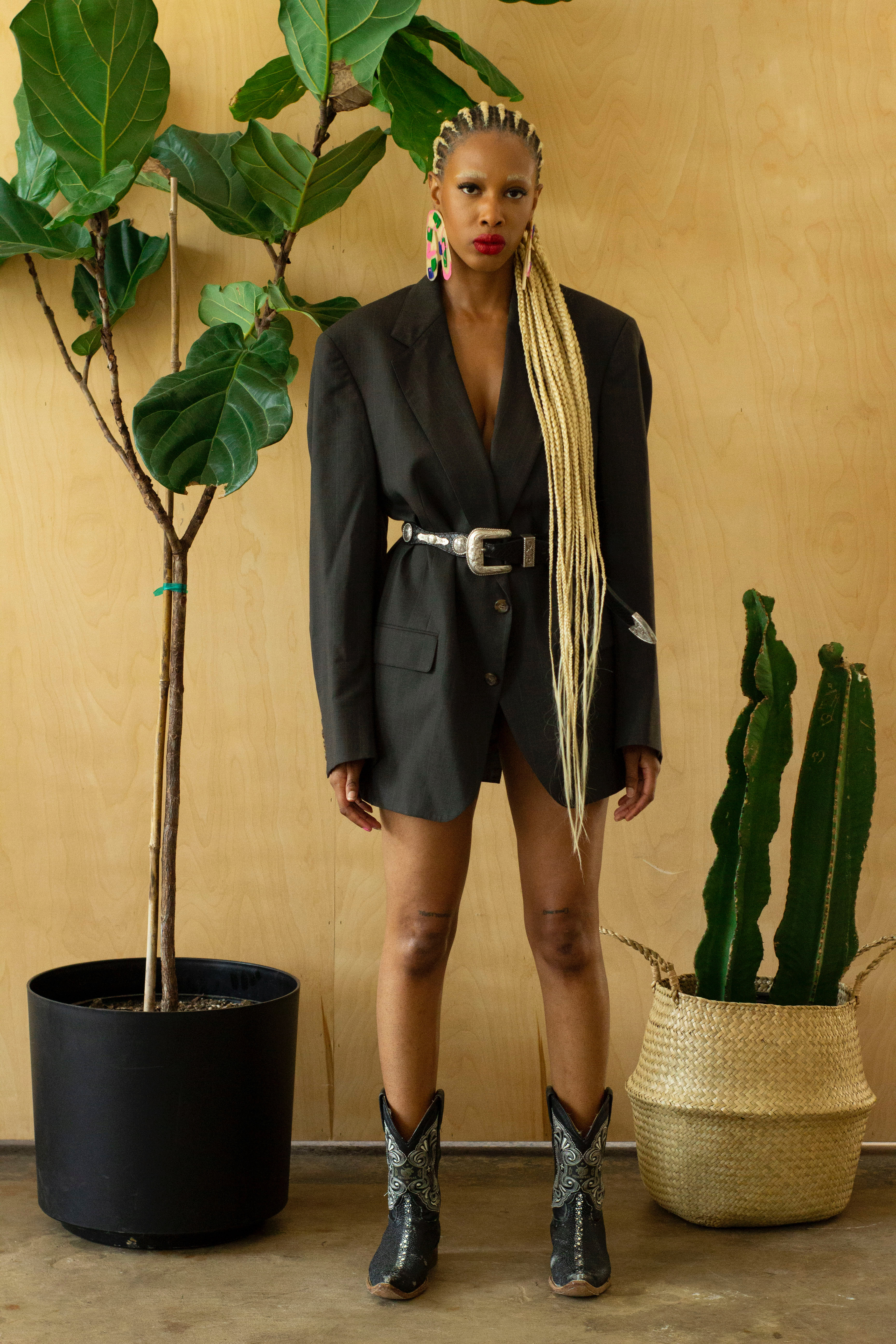 Full body portrait of Taylor in a studio surrounded by plants. She is wearing a black blazer, cowgirl boots, and her statement earrings.