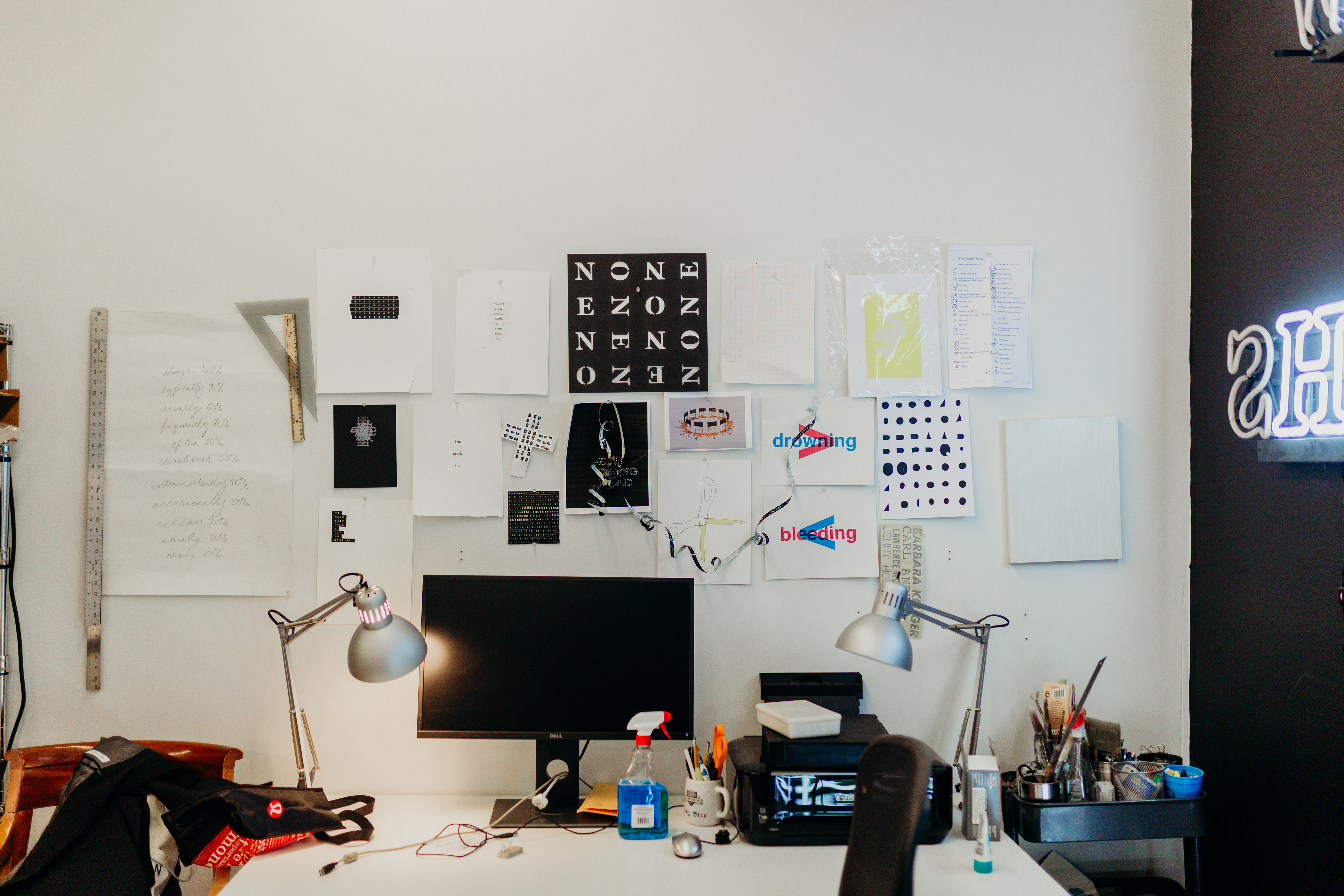 A desktop computer is on a white desk. On the wall are print outs and rulers. There is a neon sign hanging on the right wall which is painted black.
