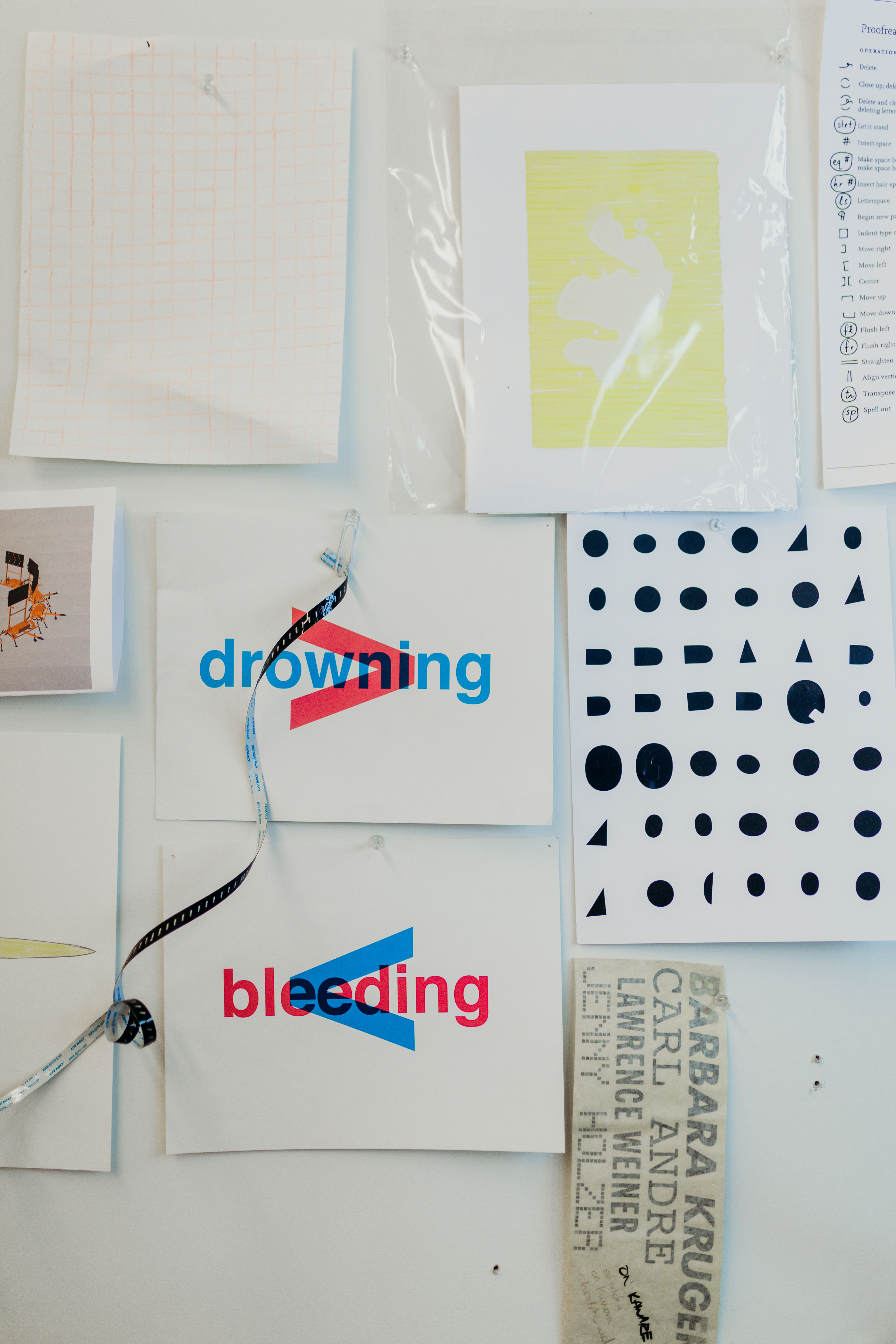 Artworks hang on a white wall. The words bleeding and drowning are superimposed over the grater than and lesser than symbols in blue and red.