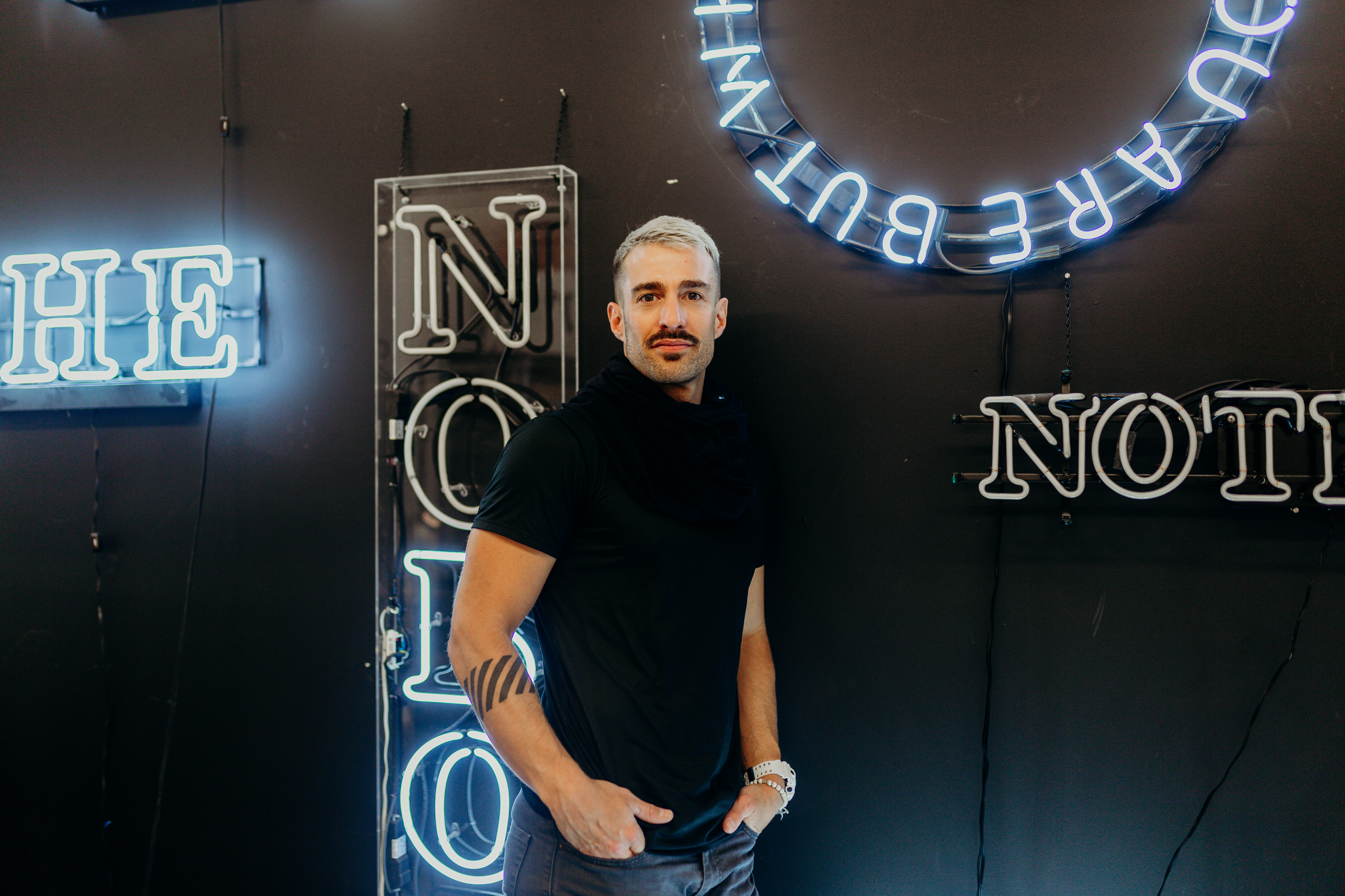 Portrait of Joel Swanson posing in front of neon signs.