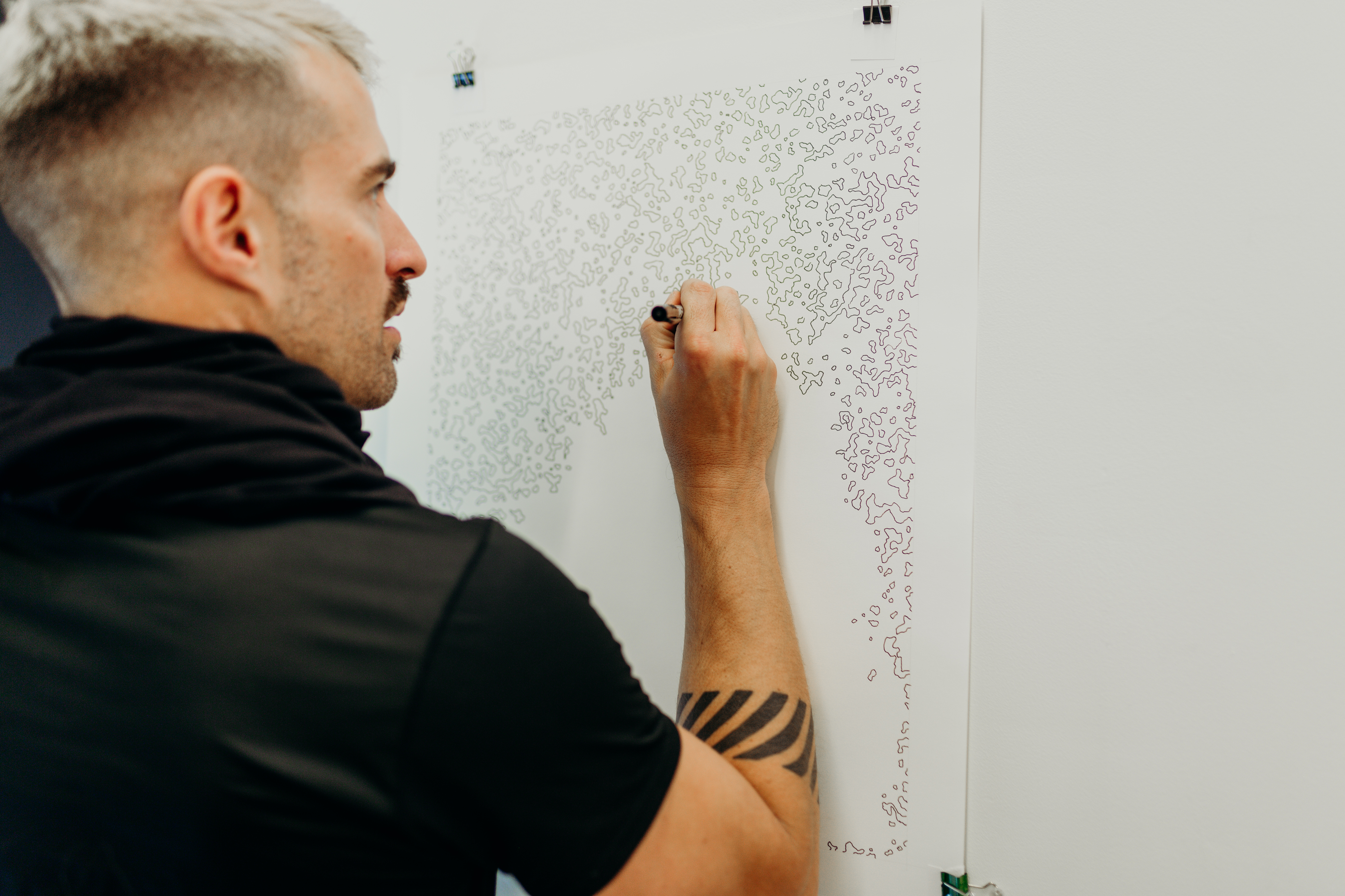 Candid shot of joel swanson drawing on a piece of paper hung on the wall. The pattern is abstract composed of several small wobbly shapes.