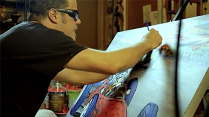 photo of John Bramblitt painting on a canvas. The image is captured from the side; in view is John's profile and an angled view of the painting he is working on. John is wearing a black t-shirt and black Oakley sunglasses, his hair is short and both hands are occupied, working on the painting. The canvas is mostly blue, with a red race car in the bottom left corner.
