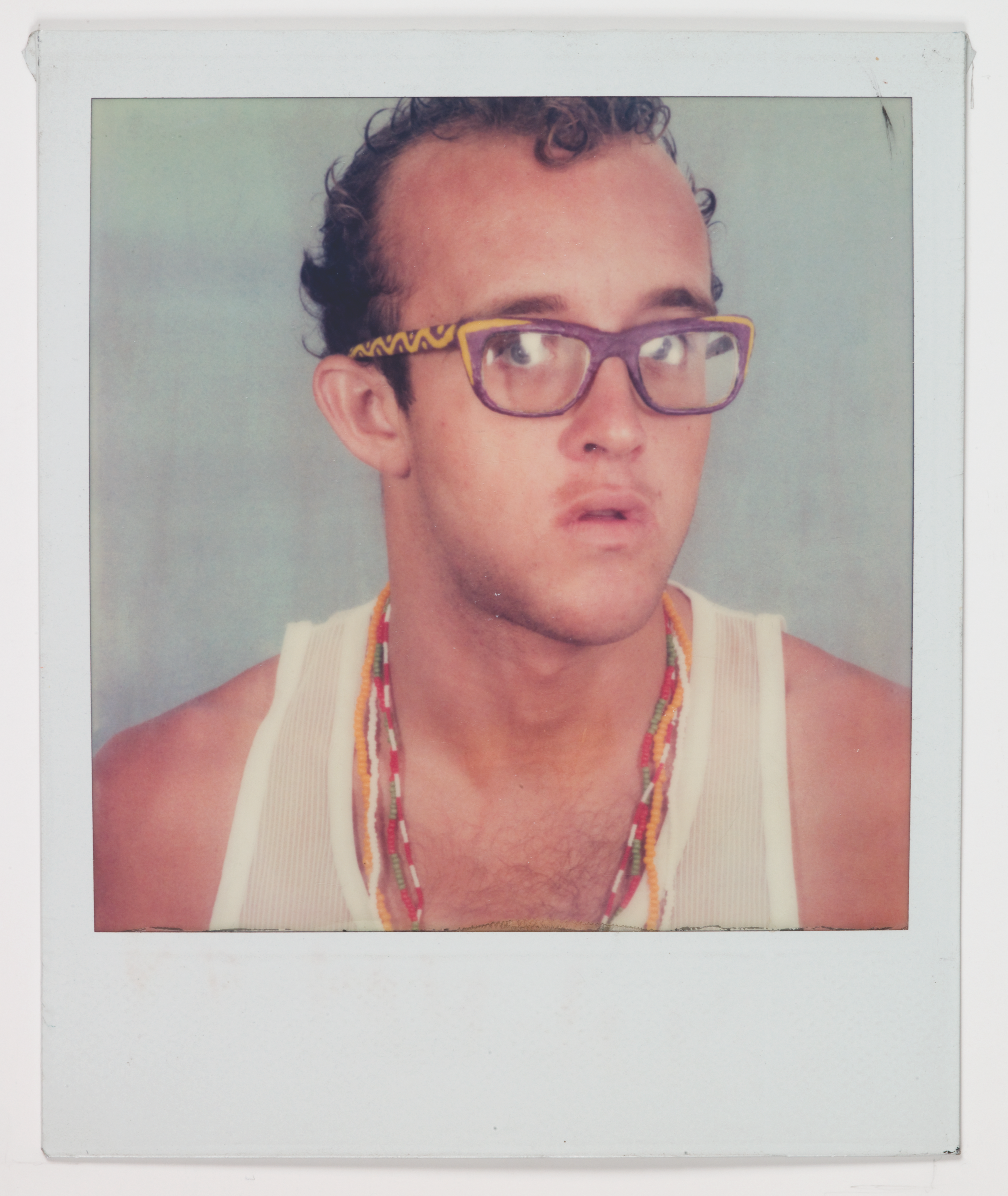 Image of artist Keith Haring. He wears purple glasses with yellow designs on the sides, a white tank top, colorful necklaces, and has short curly hair.