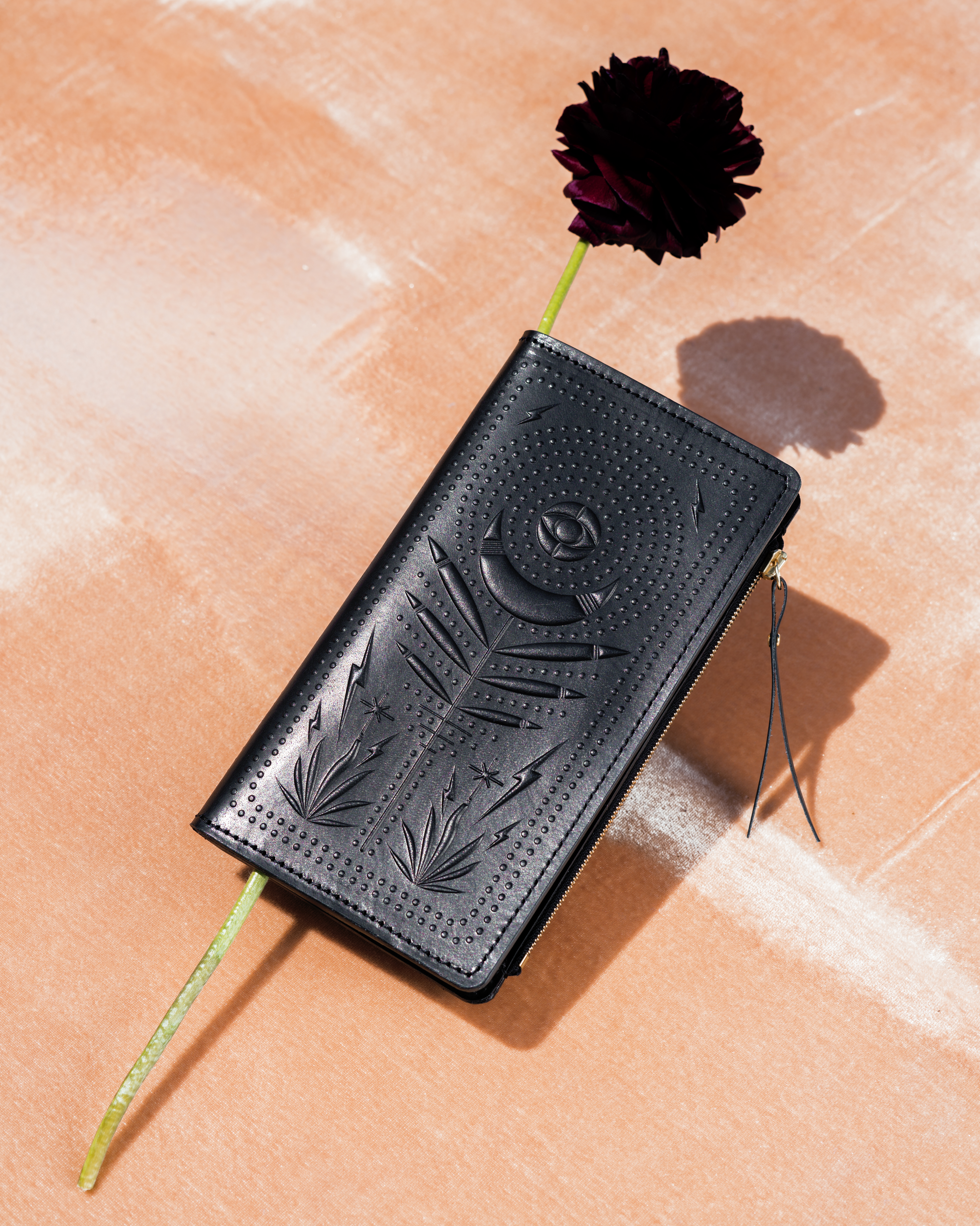 Black zip wallet with mystical design and a flower tucked inside the wallet. It's photographed under harsh light, which casts a shadow on the pink velvet backdrop the wallet is photographed on.