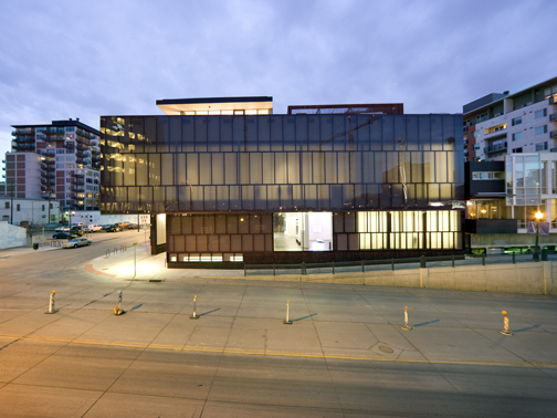 Exterior shot of the MCA Denver at dusk. The ligthing inside the museum appears to make the building glow from within.