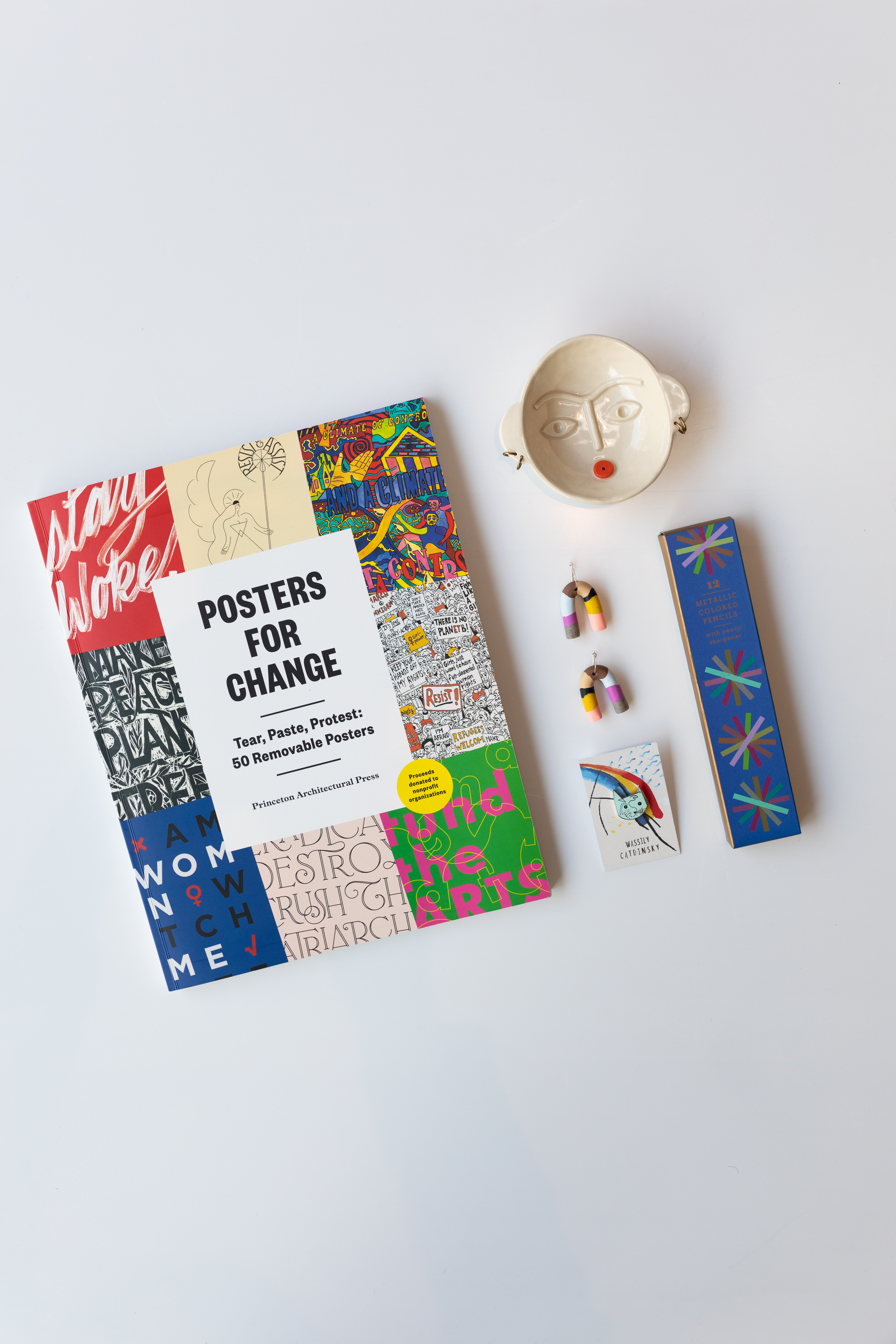 A book titled posters for change; colorful earrings; a jewlery holder with facial features on the bottom;  a cat in the style of Wassily Kandinsky, appropriately titled Wassily Catdinksy; a blue box containing 12 metallic colored pencils.