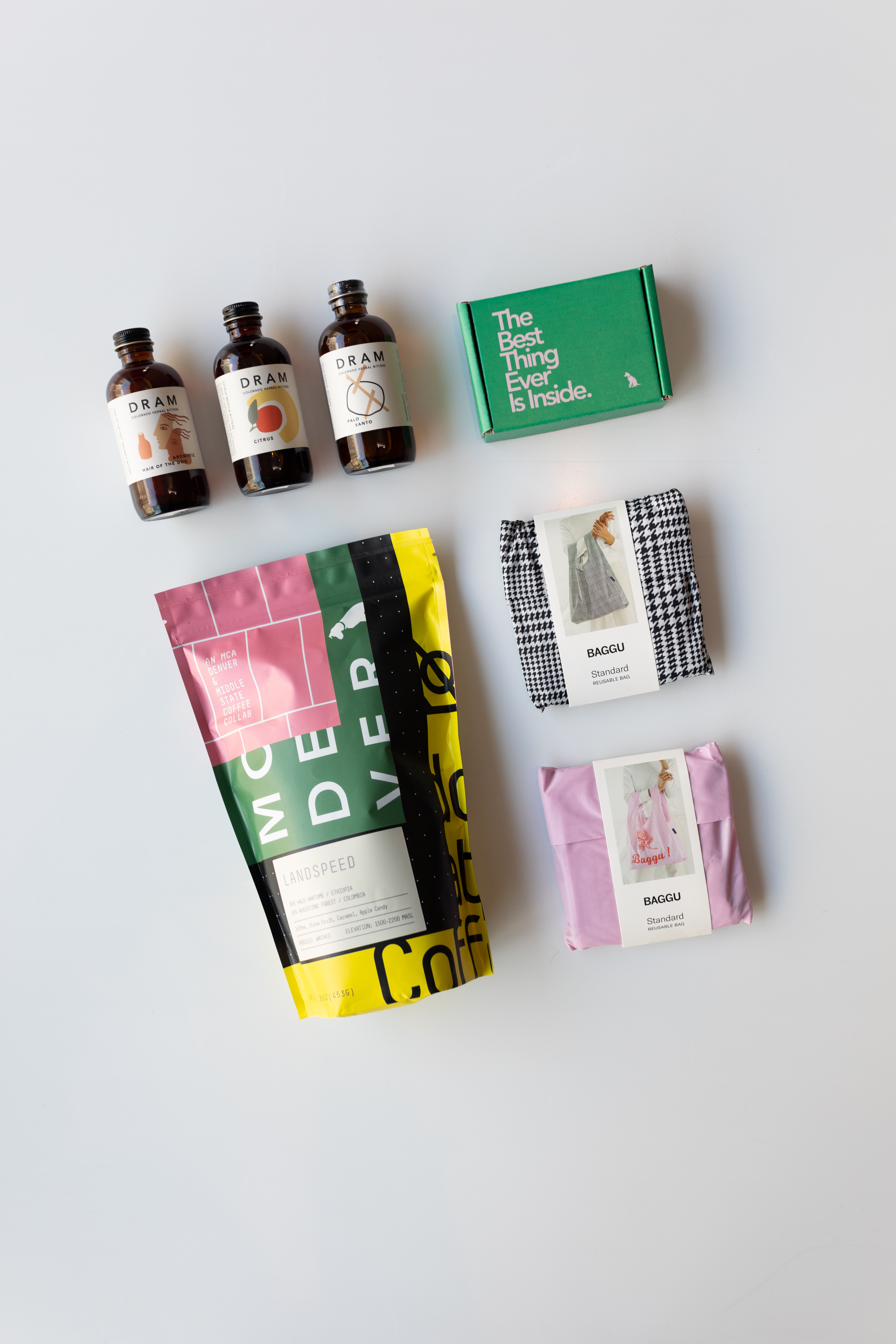 A bag of MCA Denver branded coffee from Middle State Coffee titled Landspeed; three bottls of bitters from Dram Apothecary; a green box reading The Best thing Ever is Inside; a black and white houndstooth bag; a pink bag from bagu.