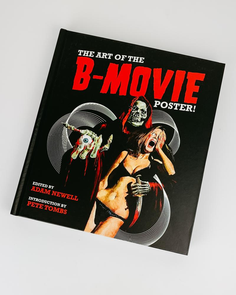 "black colored book on a white background with bold text that reads, ""The Art of the B-Movie Poster"" in red and white colored font. The figures on the cover include a creepy skeleton draped in a black hooded robe holding onto a woman in a black bikini."