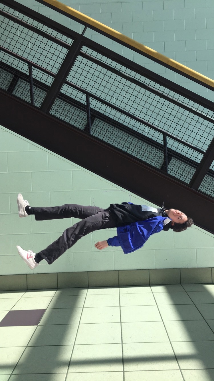 A young man appears to be suspended or falling in an indoor space.