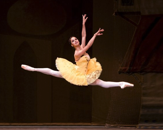 Misty Copeland in a yellow ballet tutu, in midst jump, arms elongated