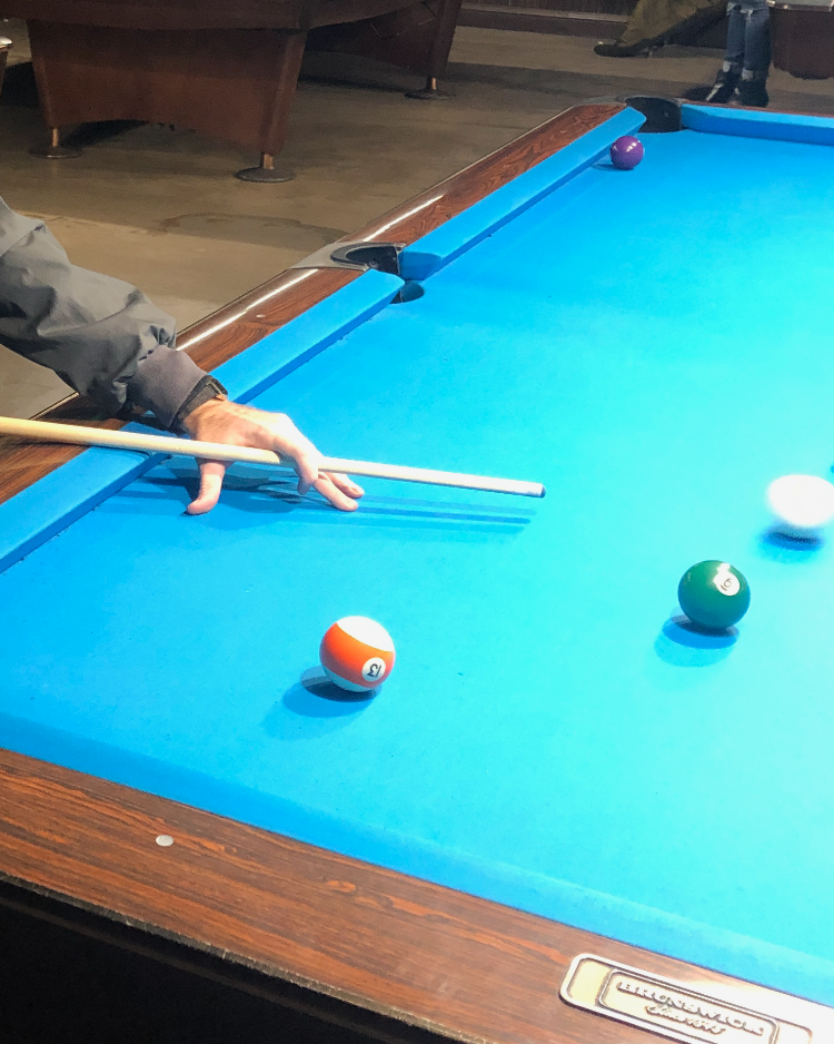 A hand is holding a cue stick above a billiards table about to strike the cue ball.