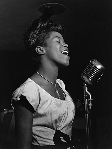 Black and White photo of the singer, Sarah Vaughan. In the 1950's, singing into a mic