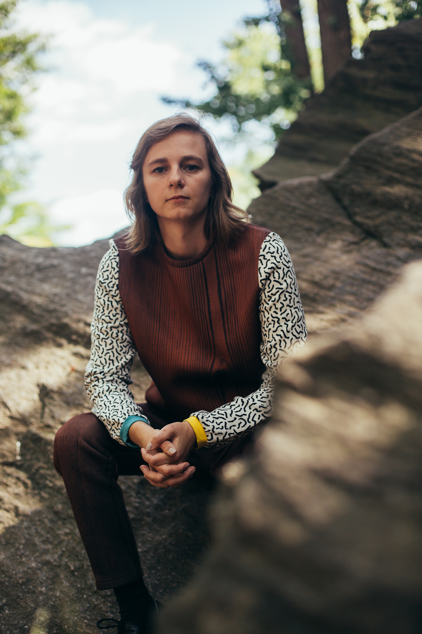 Portrait of Shannon sitting outside on a sunny day among large, flat rocks, smiling softly and looking off in another direction. She is wearing a wood grain sweatshirt and pant set. The sweatshirt has contrasting sleeves with a squiggle pattern and sleeve cuffs in two different colors