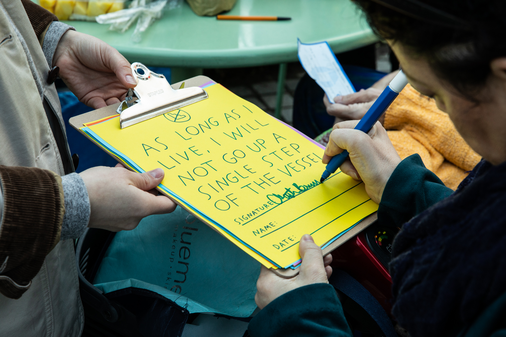 "Close up photo of someone's hands holding a clipboard for another person to sign the pledge that states, ""As long as I live, I will not go up a single step of the Vessel"" in green text written on a piece of bright yellow paper."