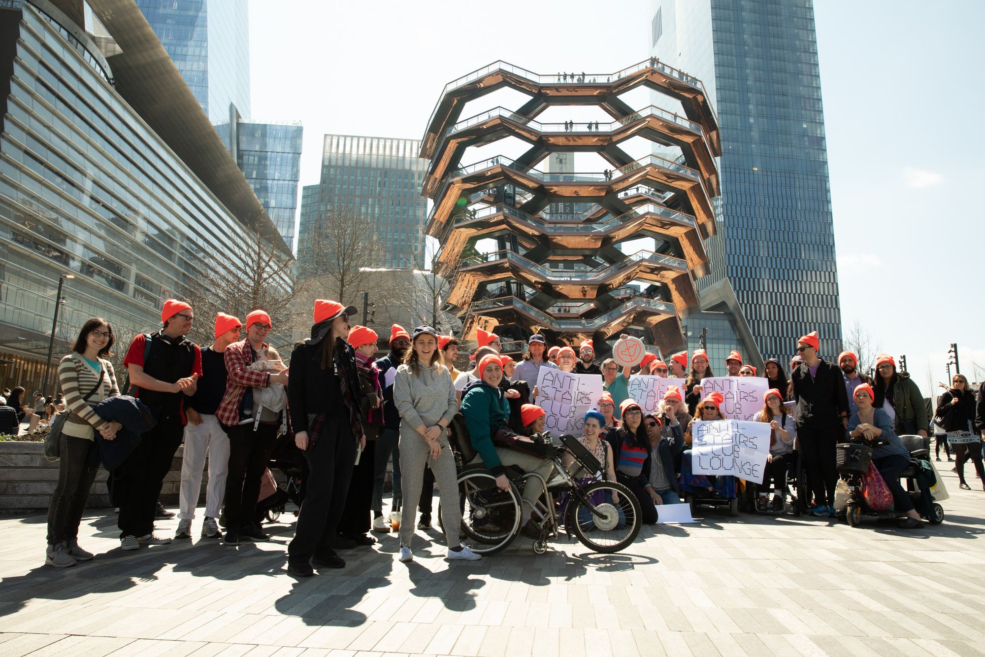 A group photo of people at Hudson Yards in Manhattan in front of the 'Vessel' — a building-sized, basket-like structure made of 154 interconnected stairways. People in the group are wearing bright orange Anti-Stairs Club Lounge beanies and holding Anti-Stairs Club Lounge signs.