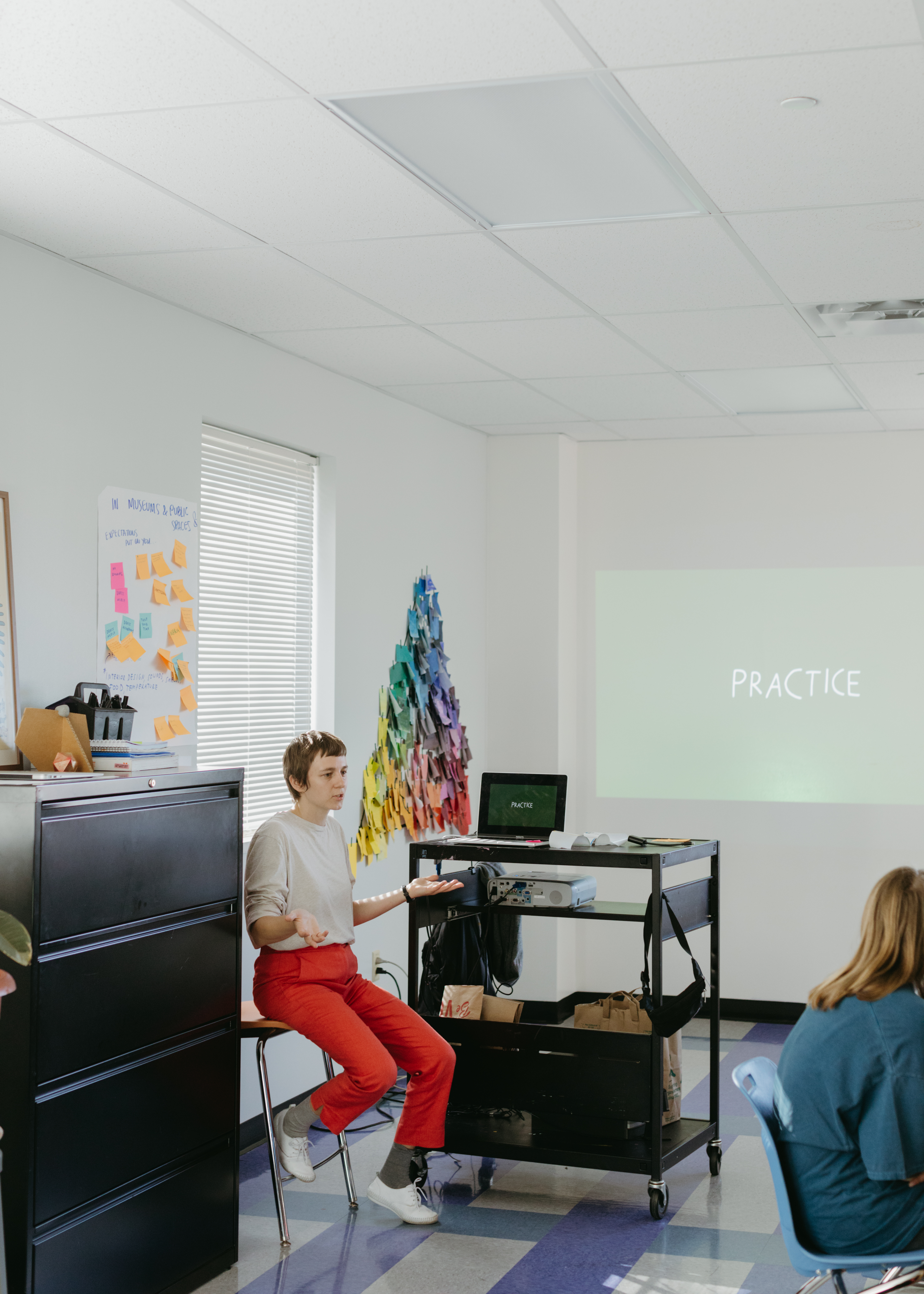 "A photo of Shannon at Girls Athletic and Leadership School (GALS), giving a presentation, with the word ""Practice"" being projected onto the wall. She is sitting in a chair next to the presentation, talking with her palms facing upwards, wearing a beige top and bright orangish, pinkish pants."