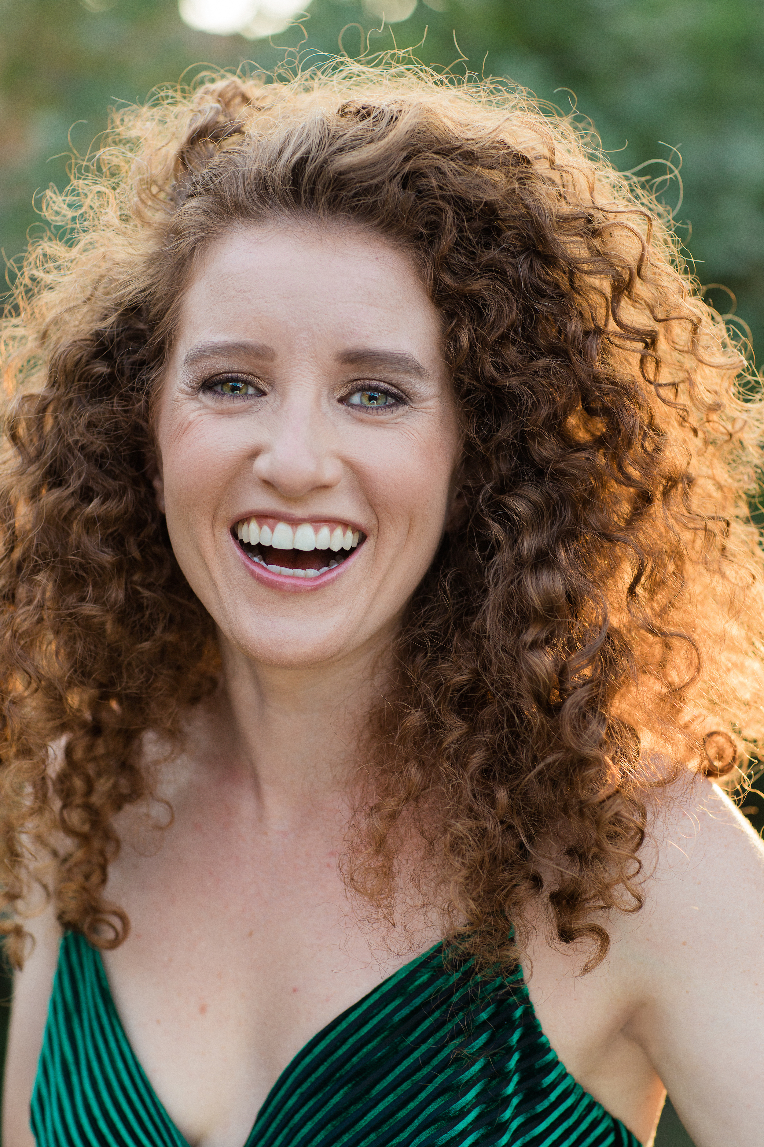 Portrait of Steph Holmbo in an outdoor setting during sunset. Her auburn hair is voluminous, curly, and seems to glow due to the sun shining through behind her. She is smiling brilliantly into the camera.
