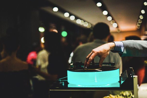 A suited hand spins a vinyl in a bar setting.