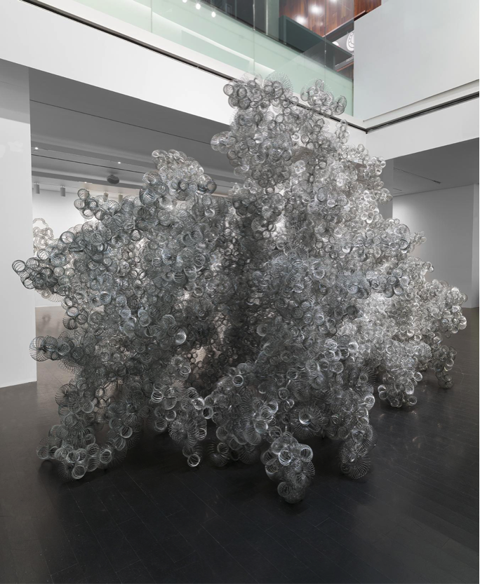 A large amorphous sculpture made up entirely of slinkies rests in a gallery space upon dark wood flooring.
