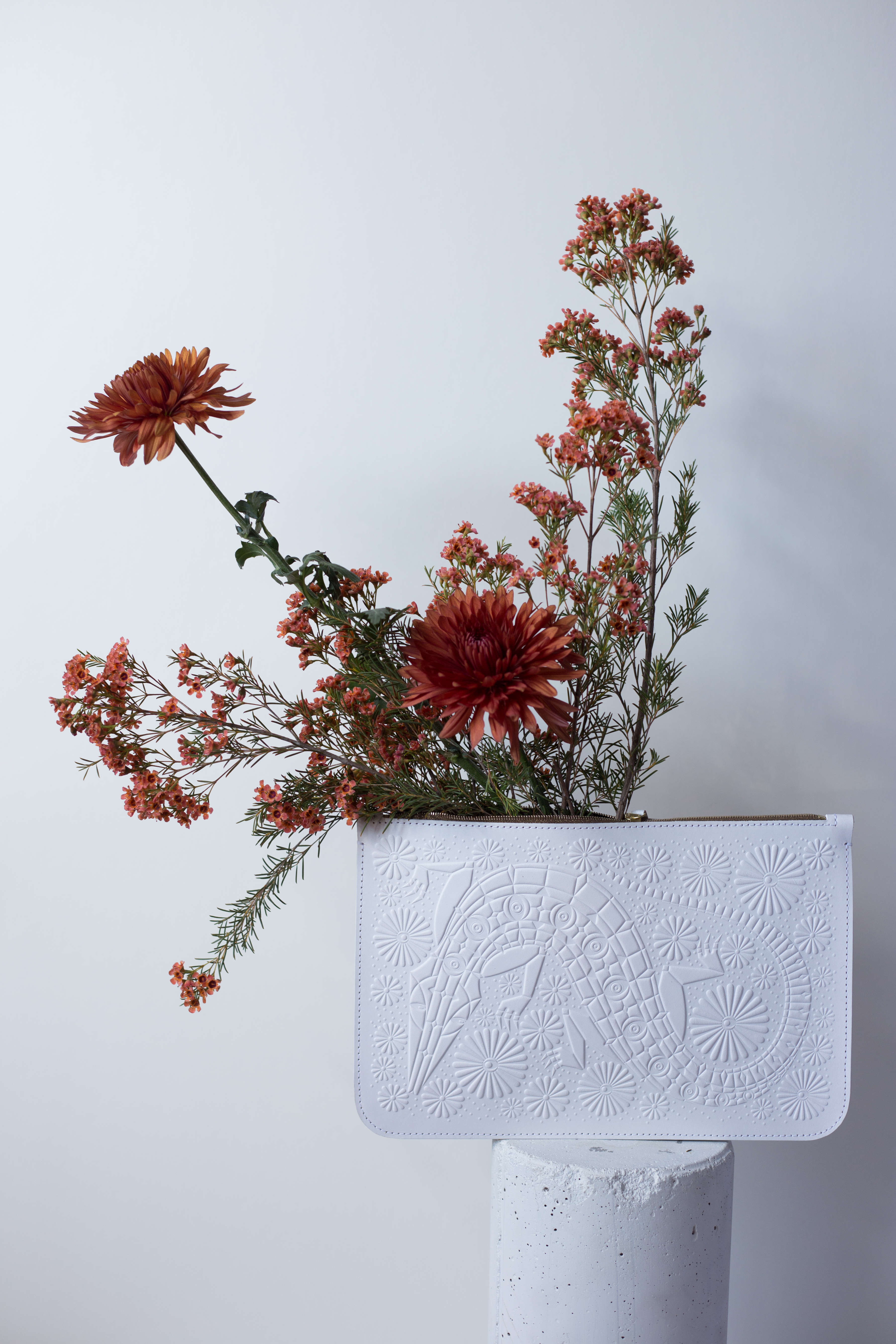 A large white leather clutch with a bold design on it, which includes a large slithering snake or reptile. The clutch is sitting on a white pedestal and has red flowers coming out of the inside of the pouch. the image is captured on a white backdrop.