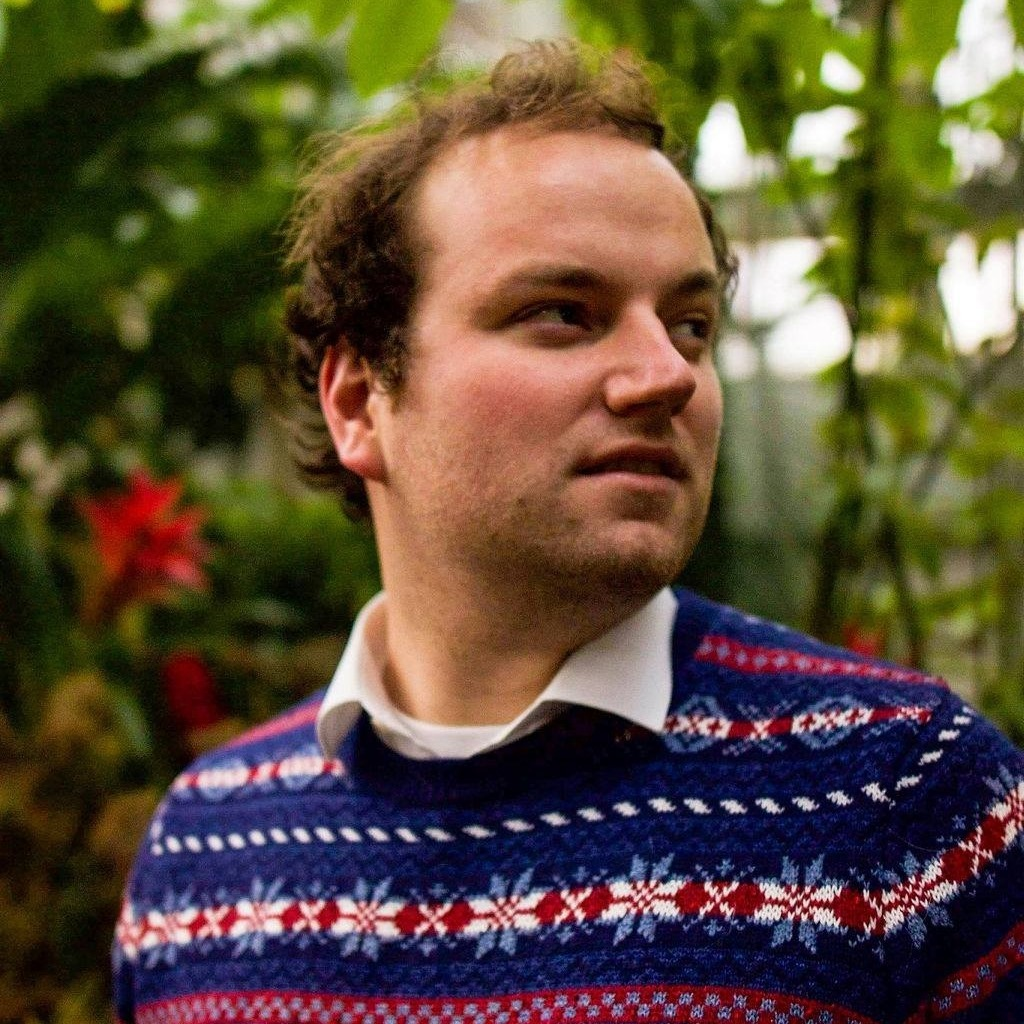 portrait of Brad in front of what looks like a lush green plants. His hair looks unkept but cool, and he is looking off into the distance with a contemplative, serious look on his face, and is wearing a festive blue and red sweater.
