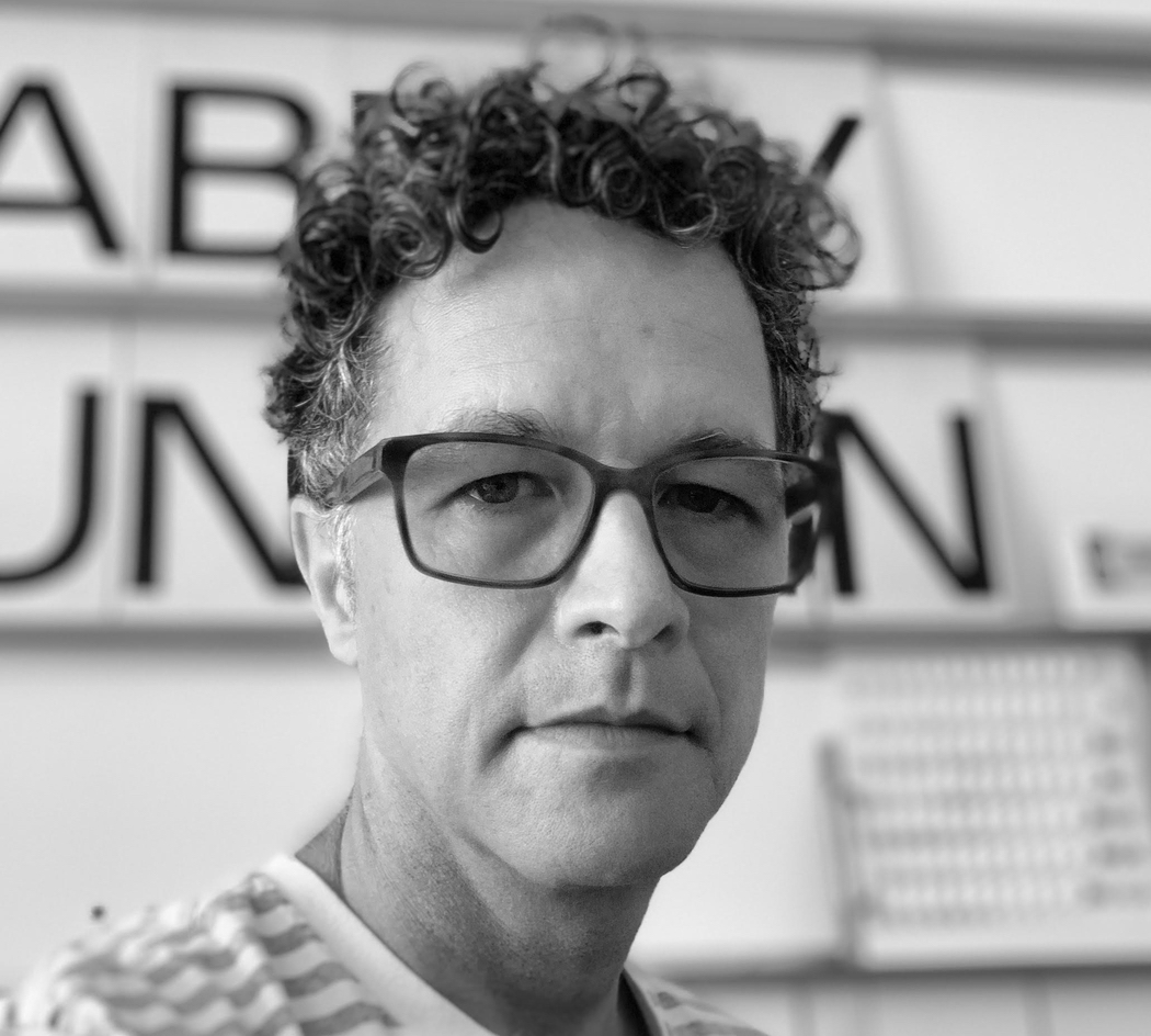 Black and white portrait of Paul, who is wearing glasses and a striped shirt. He has a serious look on his face, his hair is curly, and he is standing in front of some large text.